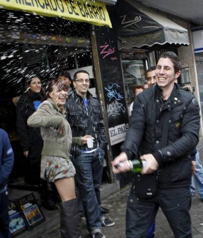 Varios jóvenes celebran su suerte con champán ante la administración 247 de Madrid, ubicada en el popular barrio de Ascao (Ciudad Lineal), donde se ha vendido íntegramente el número 70.013