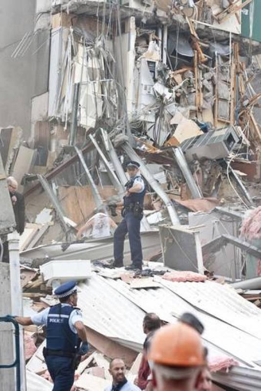 Un policia intenta coordinar las labores de rescate en el edificio de la CTV antes de que se suspendieran por razones de seguridad