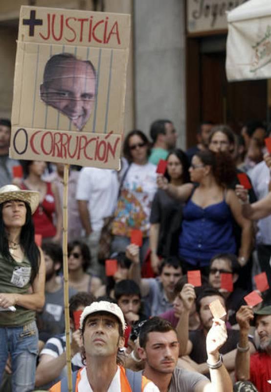 Uno de los manifestantes porta una pancarta con la fotografía del president de la Generalitat, Francisco Camps.