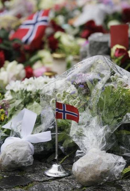 A Norwegian flag stands among flowers placed on the market square outside the Oslo cathedral to mourn the victims of a bomb blast and a rampage