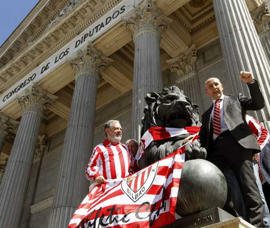 Los diputados del PNV Pedro Azpiazu y Josu Erkoreka posan junto a uno de los leones que preside la entrada principal al edificio del Congreso de los Diputados con banderas del Athletic de Bilbao.
