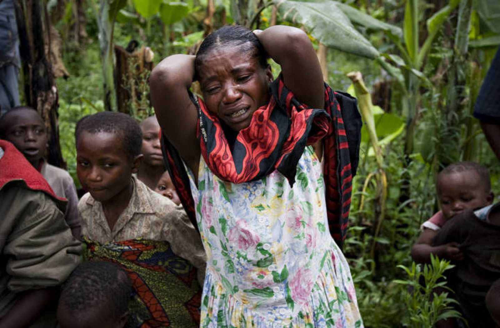 Woman cries at the grave of eight-month old Alexandrine Kabitsebangumi in eastern Congo