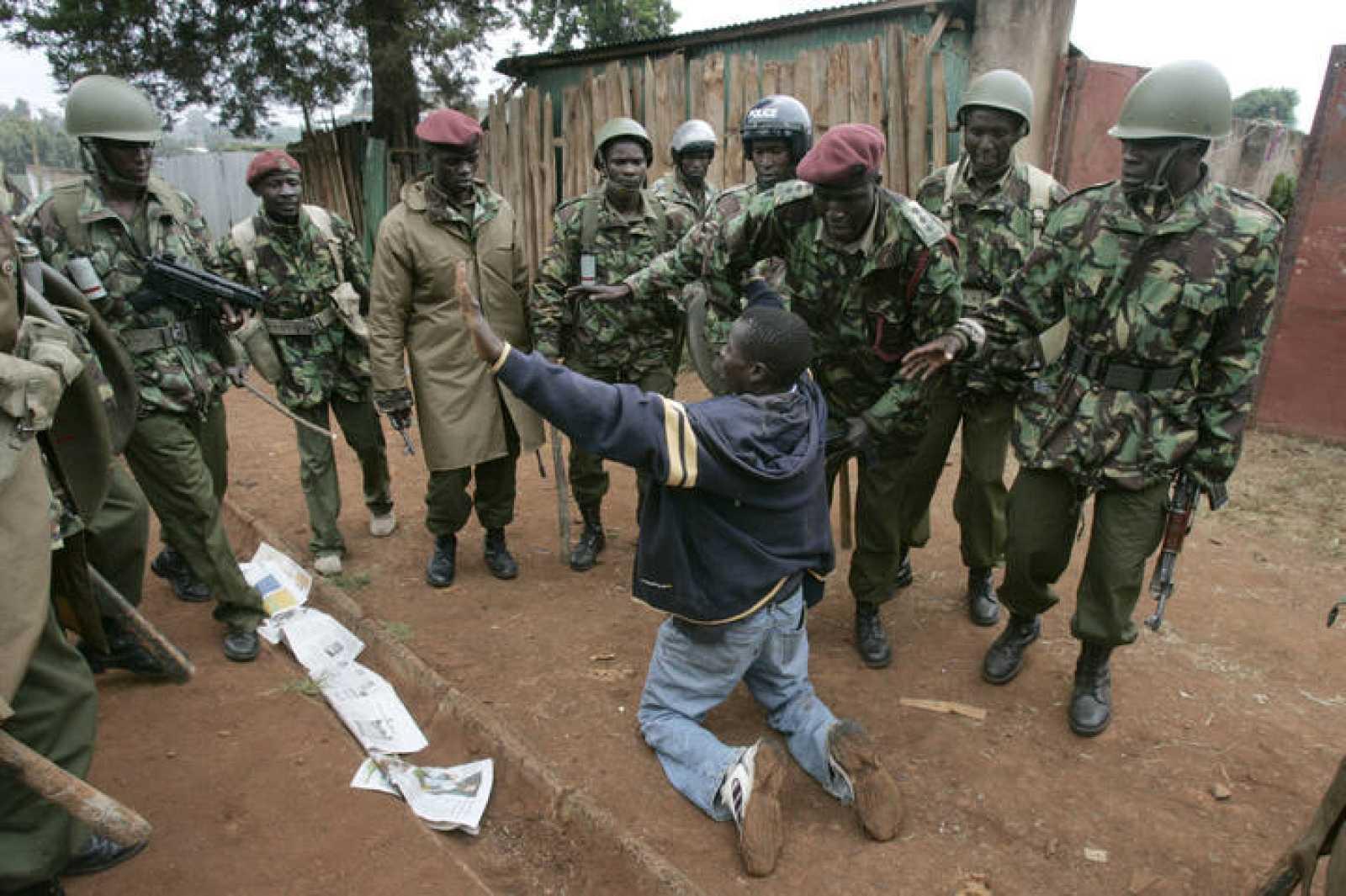 Un ciudadano pide la misericordia de policías antidisturbios durante las protestas en los barrios de Kibera en Nairobi.