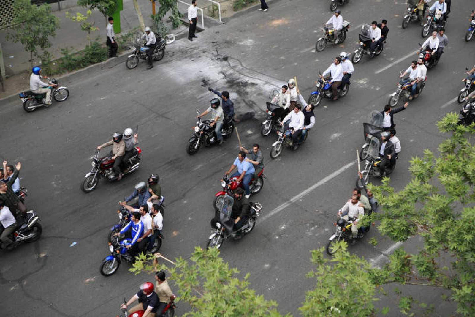 Grupos de manifestantes iraníes armados con palos recorren en moto el centro de Teherán.