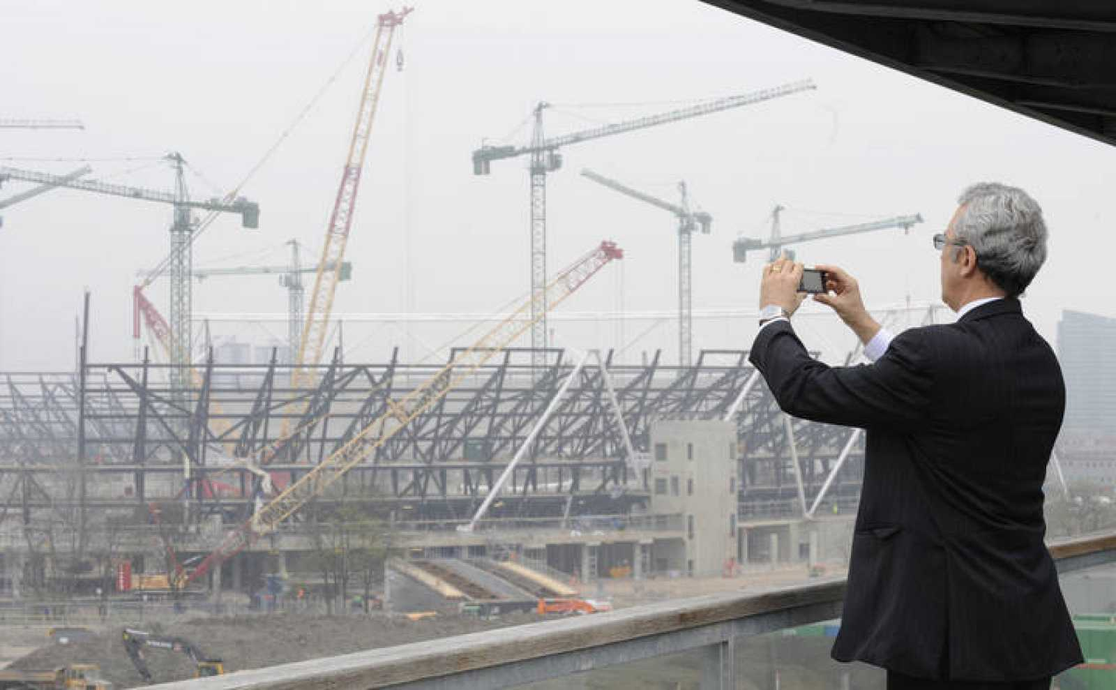 A man photographs the main Olympic Stadium construction at Stratford in east London