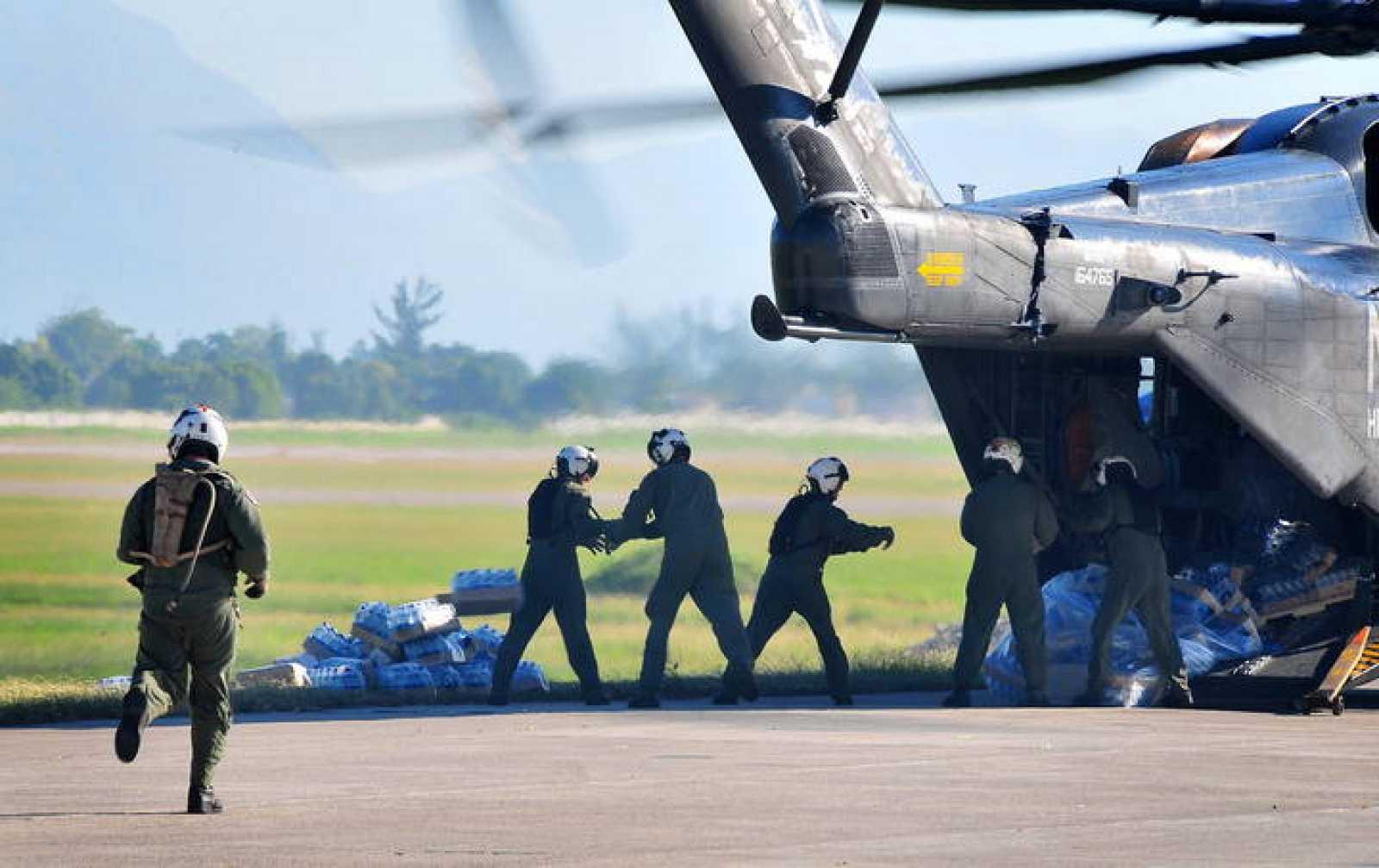 Soldados estadounidense descargan alimentos y suministros de un helicóptero de la Marina en Puerto Príncipe.