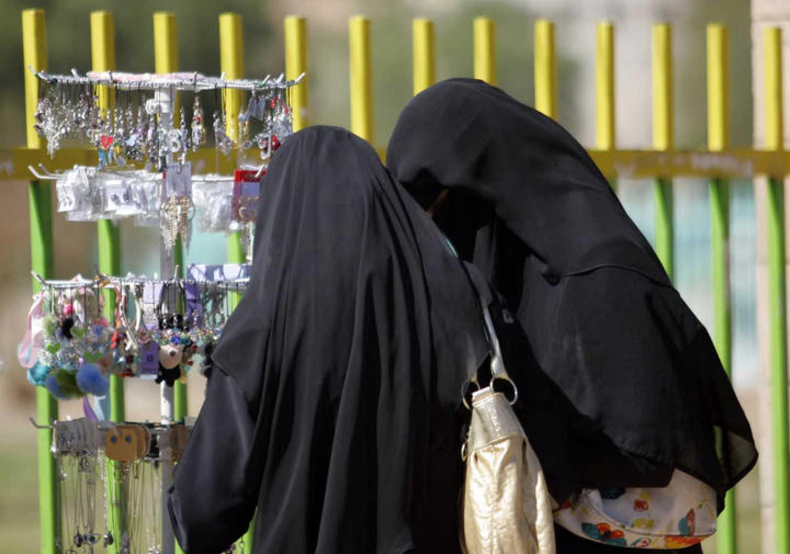 Dos mujeres vestidas con velos compran accesorios en un puesto ambulante en Sanaa en Yemen.