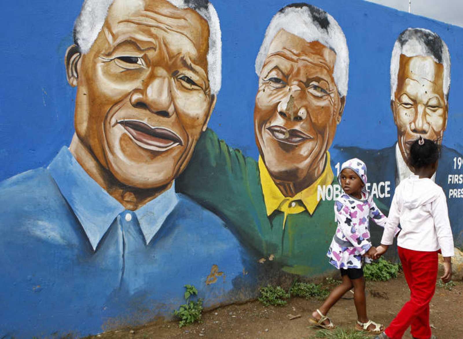 Dos niñas pasean junto a un grafiti del ex presidente de Sudáfrica Nelson Mandela en Soweto.