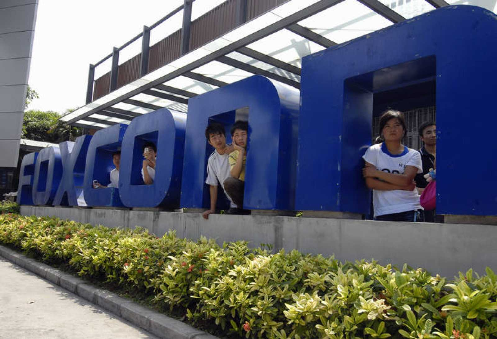 Workers stand at the gate of a Foxconn factory in the township of Longhua in Shenzhen