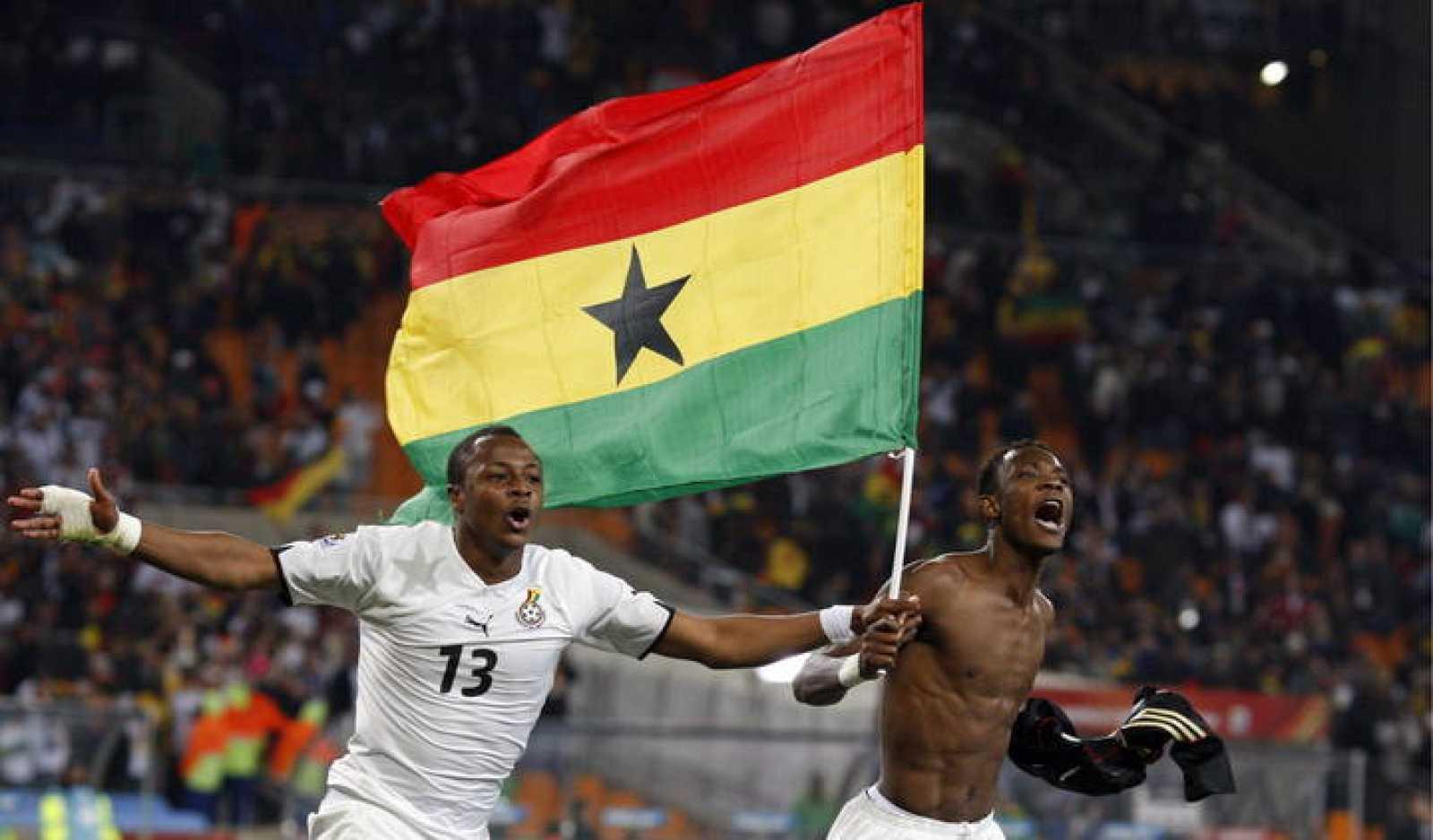 Los jugadores ghaneses Andre Ayew y John Pantsil celebran con una bandera nacional el pase de su selección a octavos.