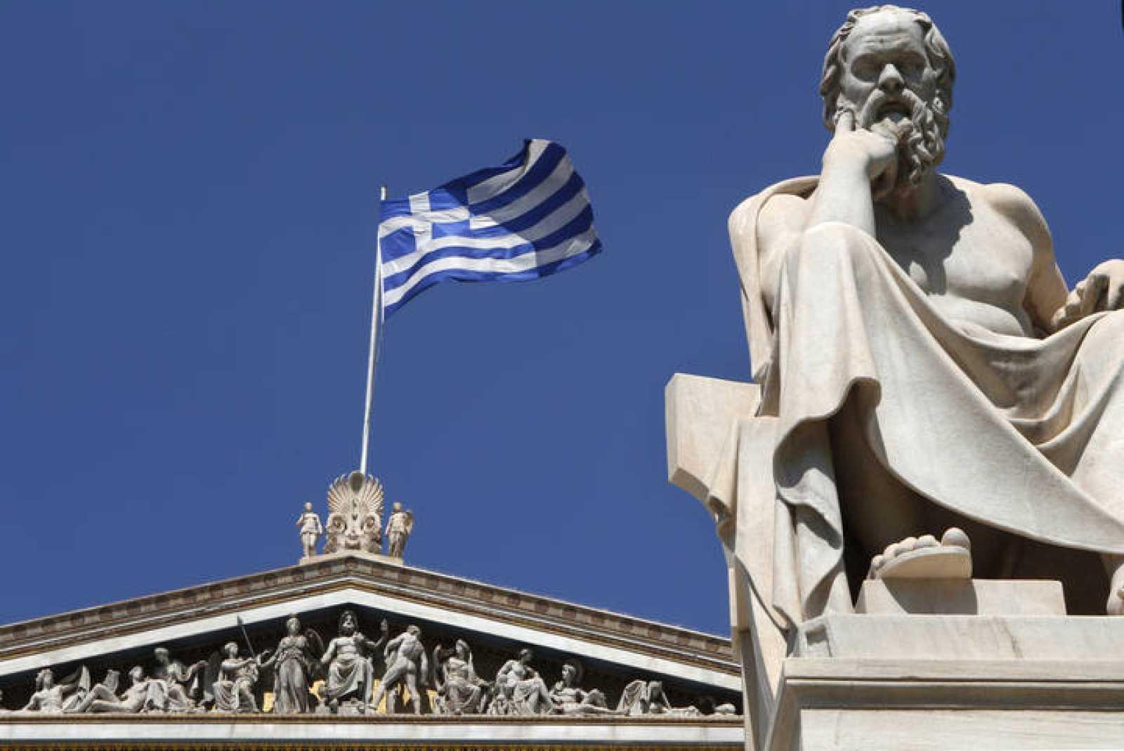 Una bandera griega ondea detrás de la estatua de Sócrates en Atenas