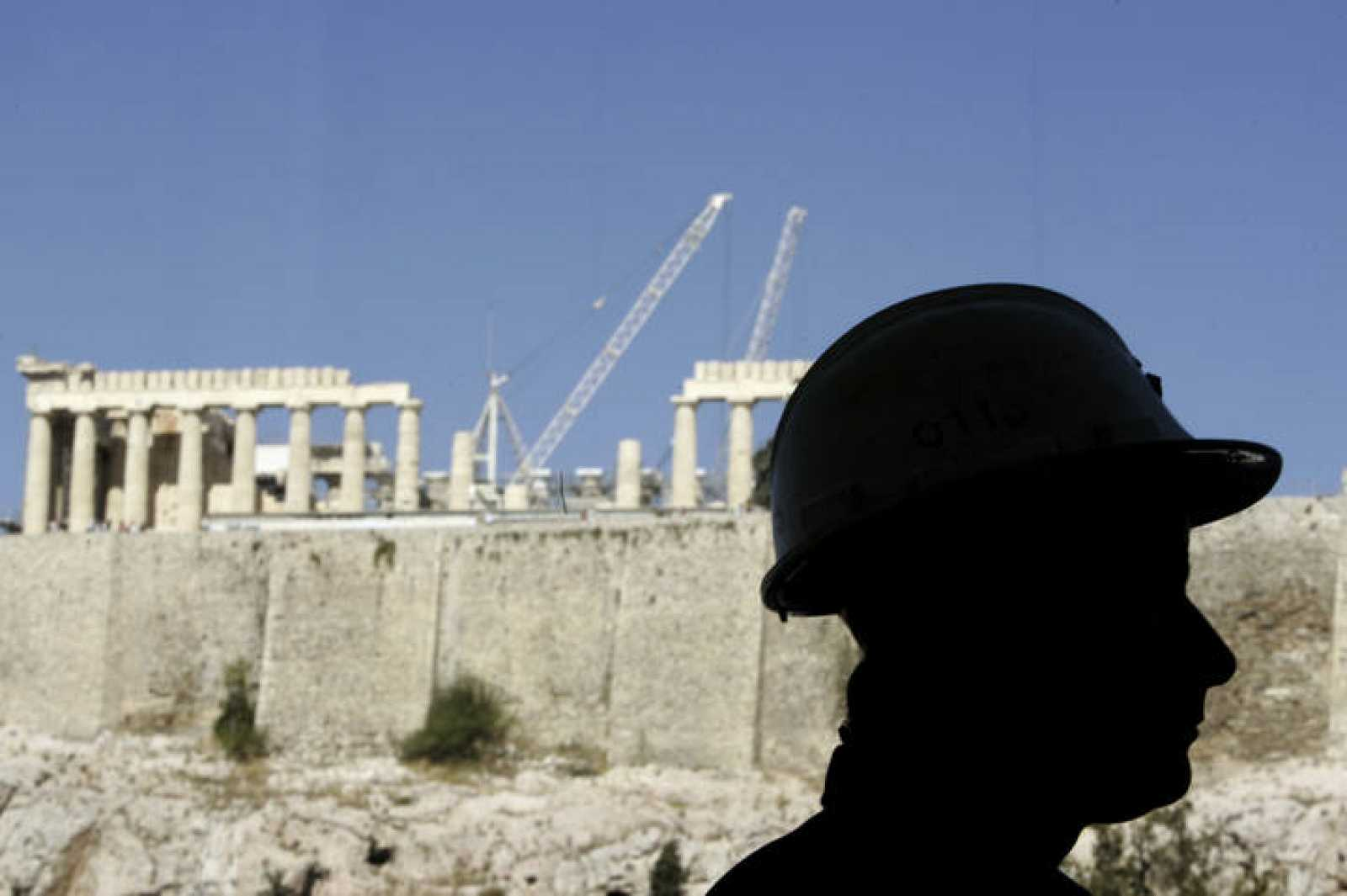 A worker is silhouetted in front of the temple of the Parthenon as he stands inside newly built Acropolis museum in Athens