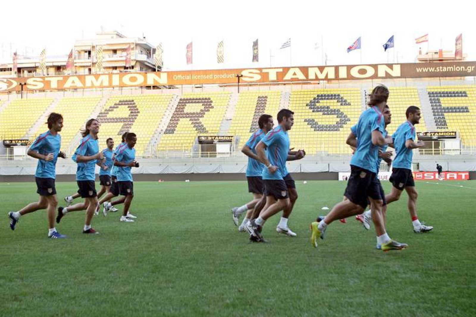 Los jugadores del Atlético de Madrid corren en el estadio del Aris de Salónica.