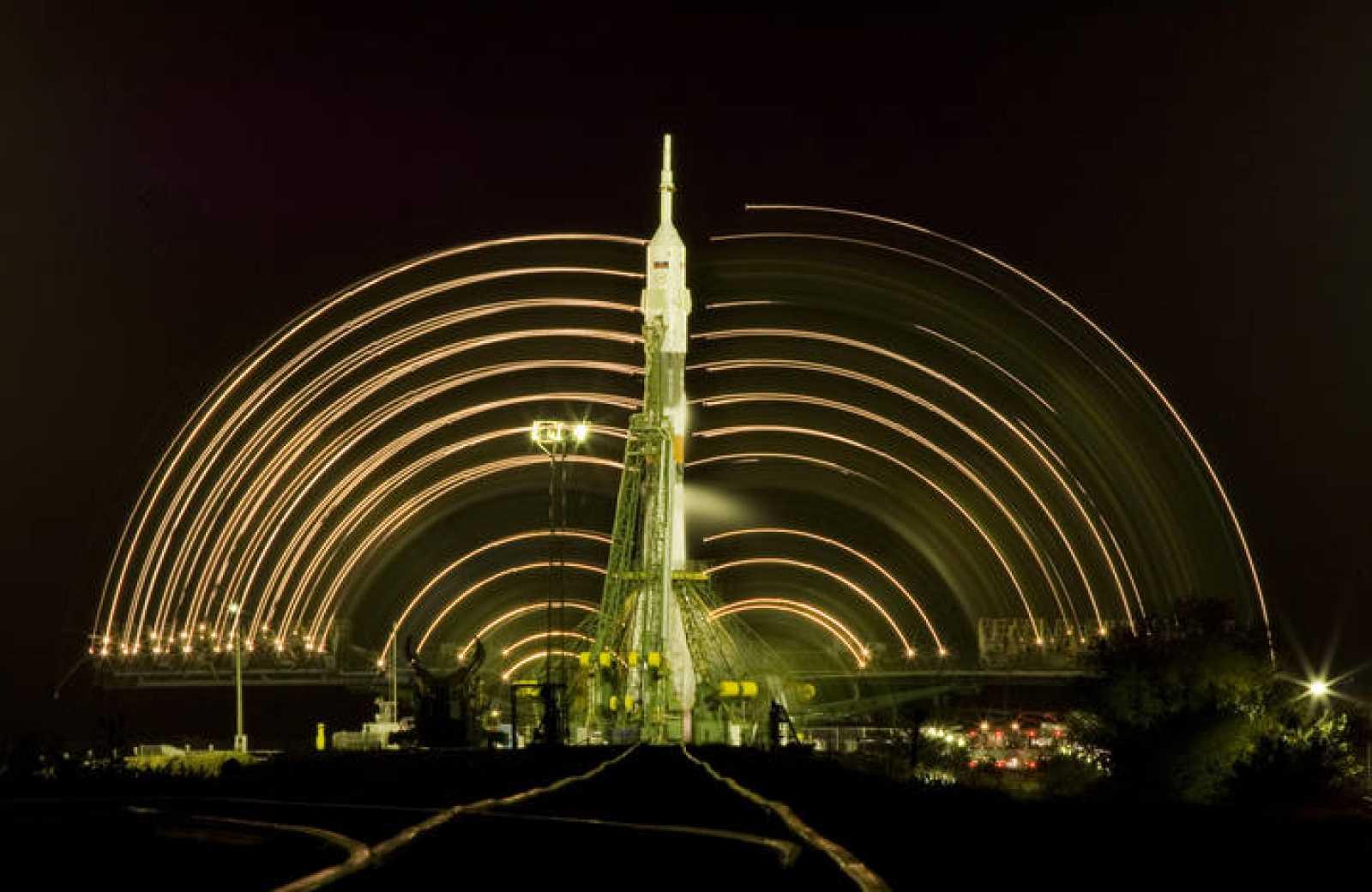 Las  luces de las torres de servicio se mueven alrededor de la nave Soyuz en esta fotografía de larga exposición.