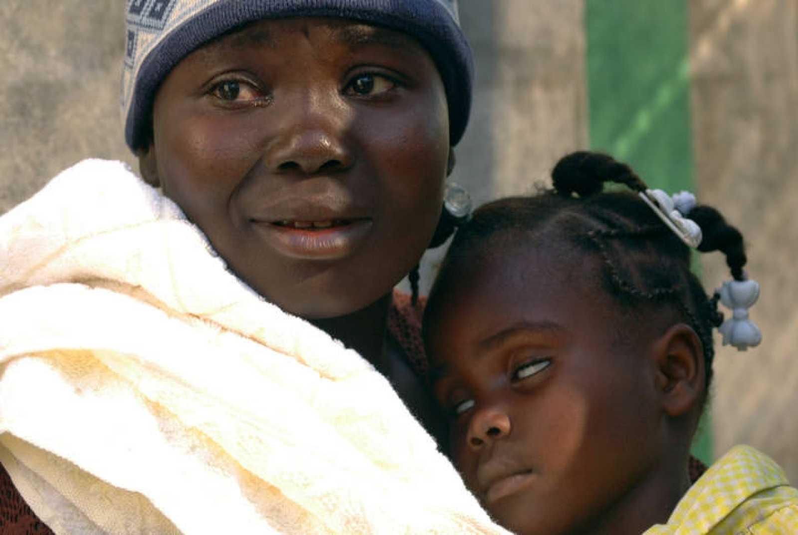 Una residente en Haití sostiene a su bebé, que está sufriendo de cólera.