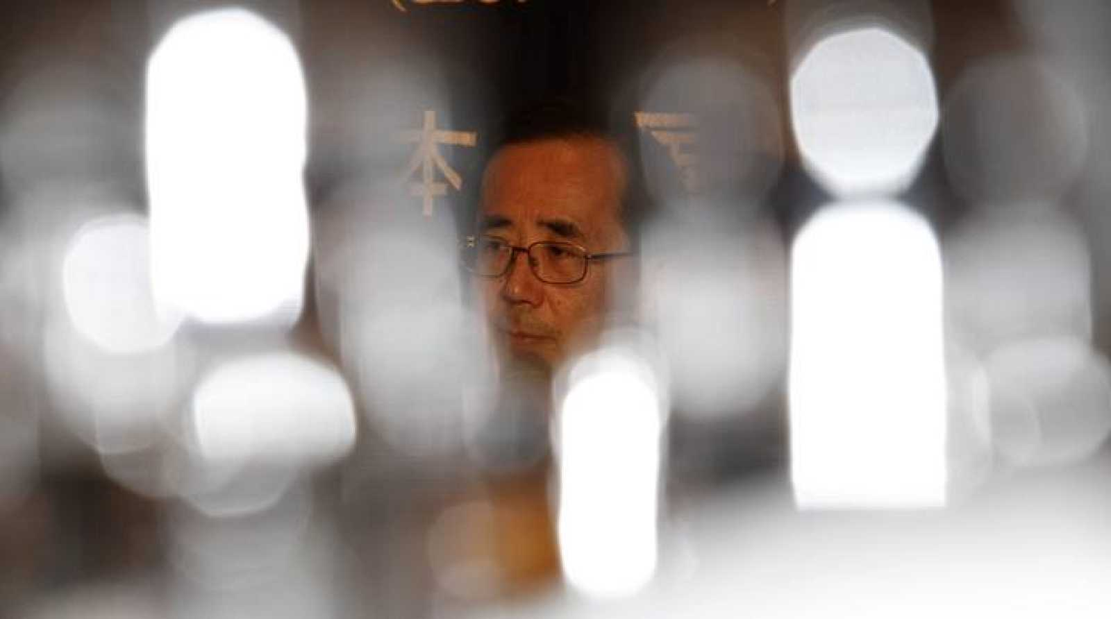Bank of Japan Governor Masaaki Shirakawa is seen through reflections on glasses during a news conference in Tokyo