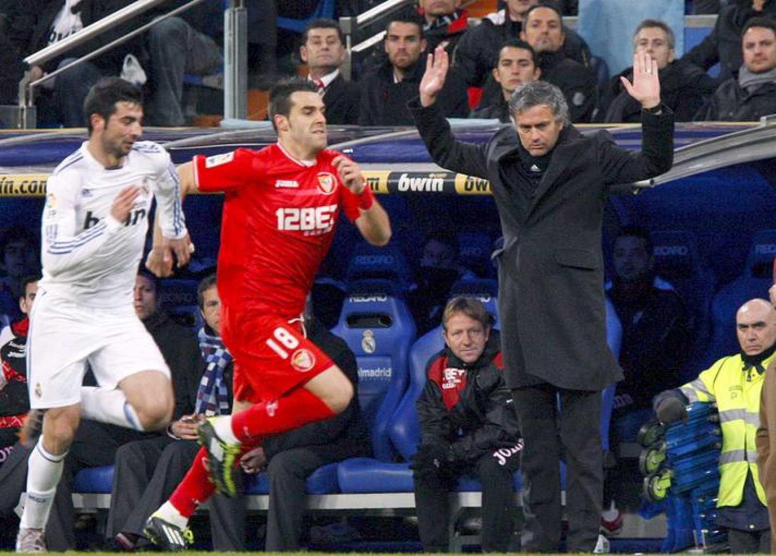 El madridista Albiol corre con el sevillista Negredo ante la mirada de Mourinho.