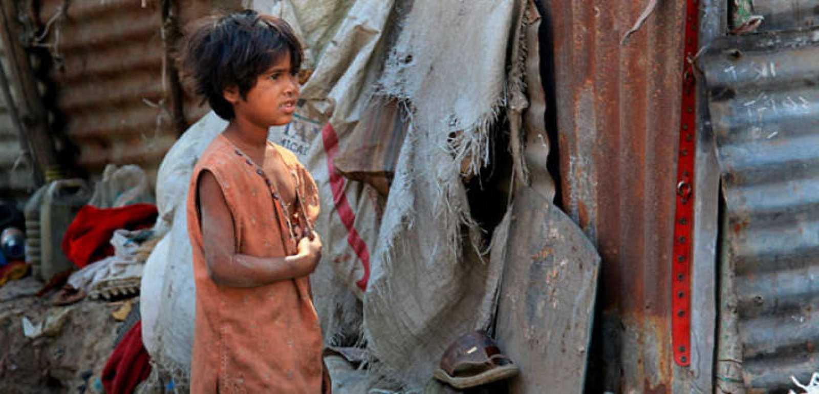 Un niño trapero indio llamado Jhuma Das espera a su madre cerca de un suburbio en la ciudad de Calcuta, en la India. Miles de personas, en su mayoría mujeres, recogen trapos y otros materiales de vertederos.