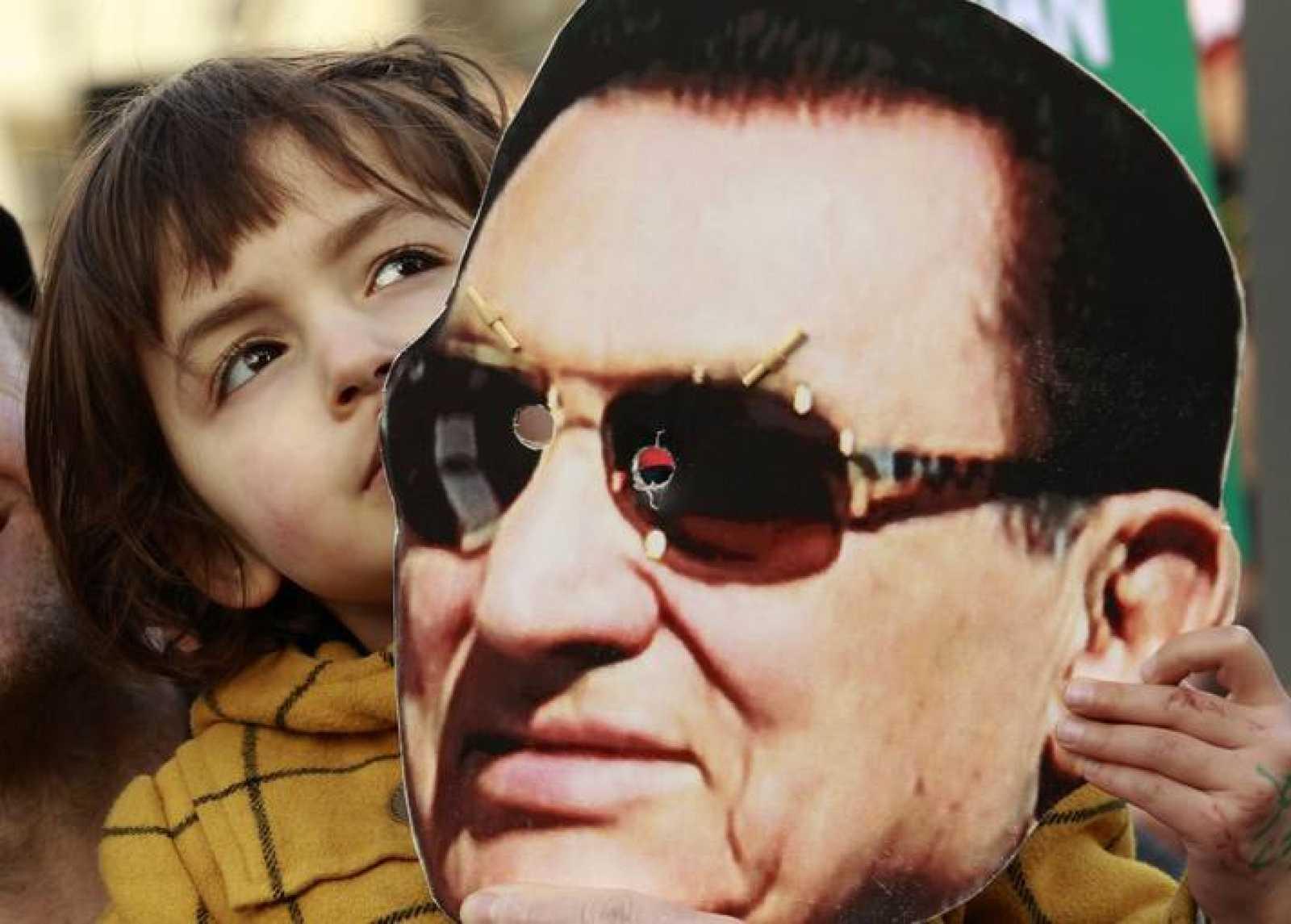 Una niña sostiene una máscara del expresidente Hosni Mubarak