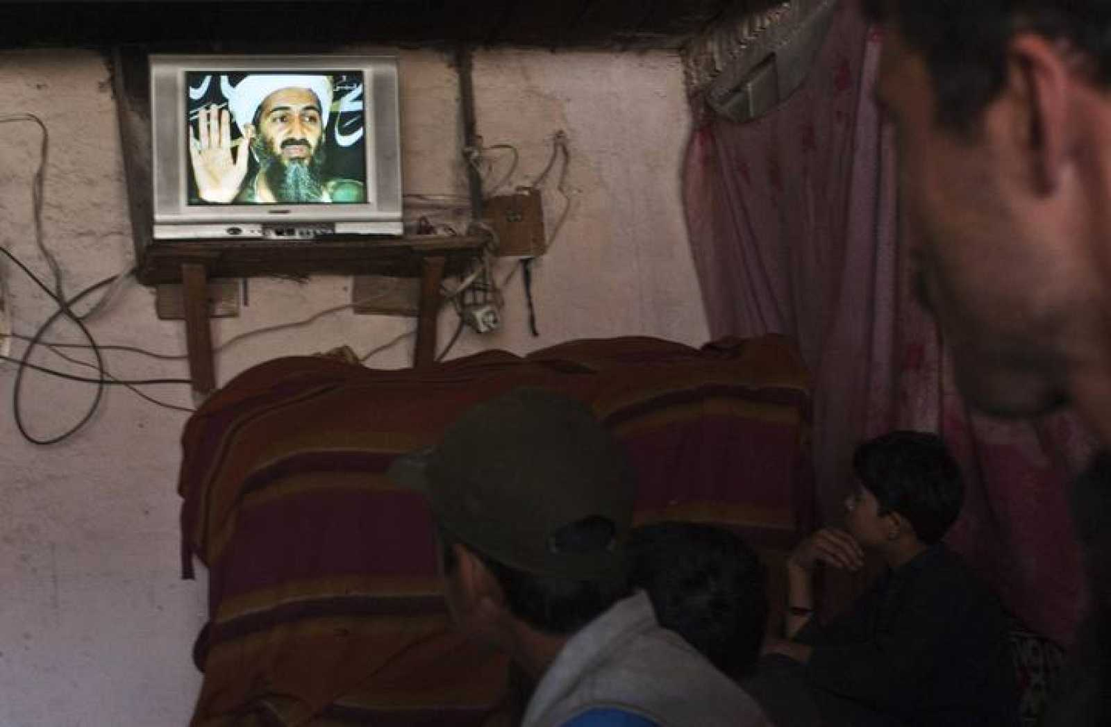 Locals watch an Afghan local television channel news telecast about Osama Bin Laden's death, at a resturant in Kabul