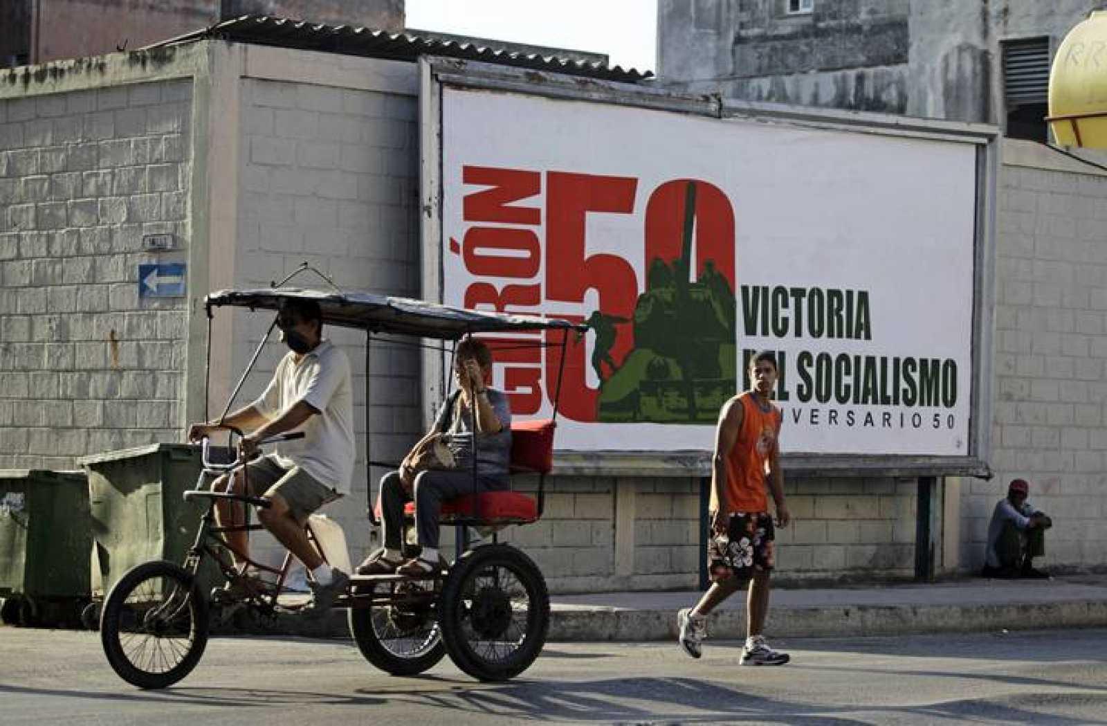 Un hombre lleva a una mujer en su triciclo taxi junto a un cartel que celebra el 50 aniversacio del incidente de Bahía de Cochinos.