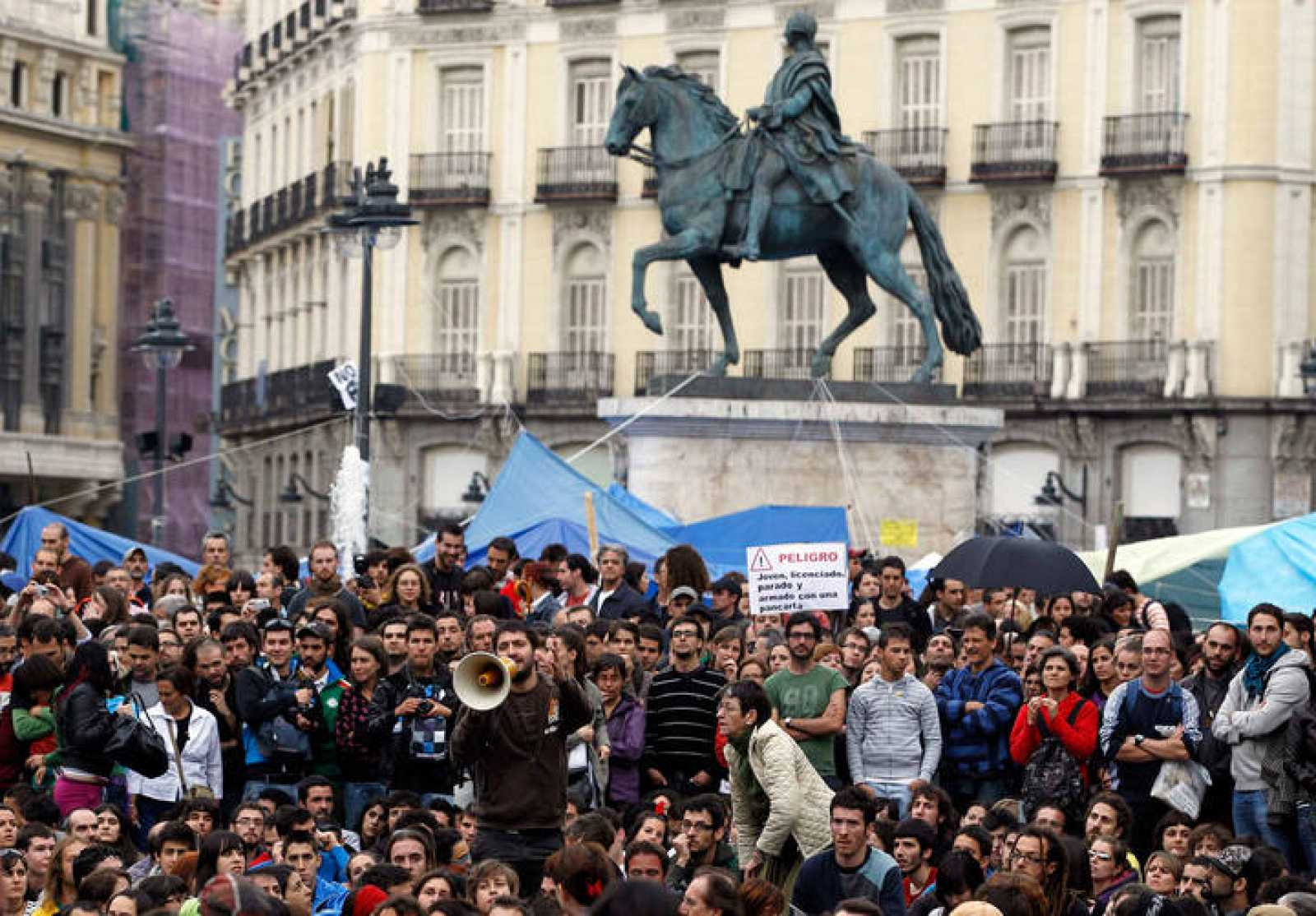 Manifestantes escuchan a los portavoces del movimiento 15-M