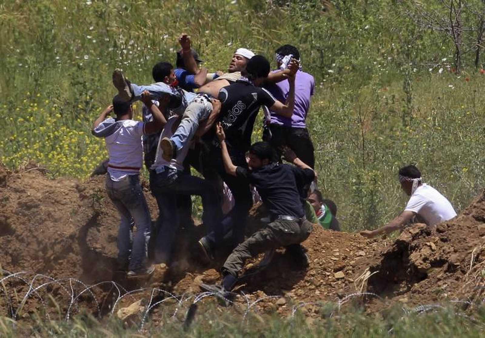 Un manifestante herido es llevado a la frontera para recibir ayuda.