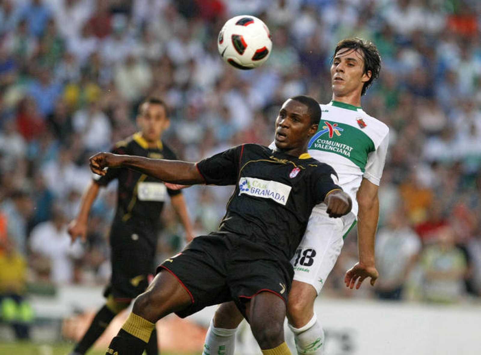 El defensa del Elche Sergio Pelegrín lucha un balón con el delantero nigeriano del Granada Odion Jude Ighalo.