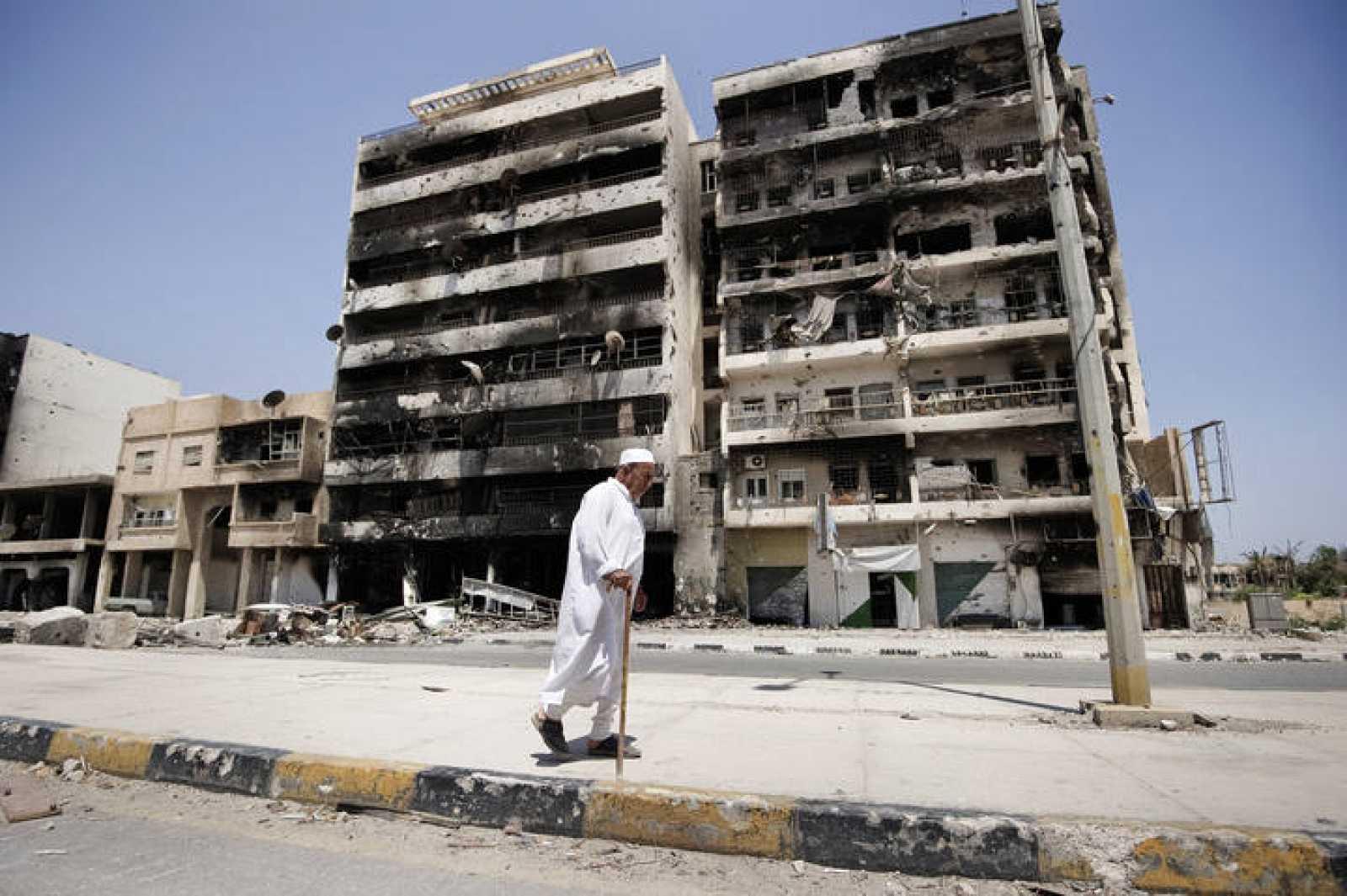 Un hombre pasa junto a un edificio dañado en los bombardeos de la ciudad de Misrata, en Libia