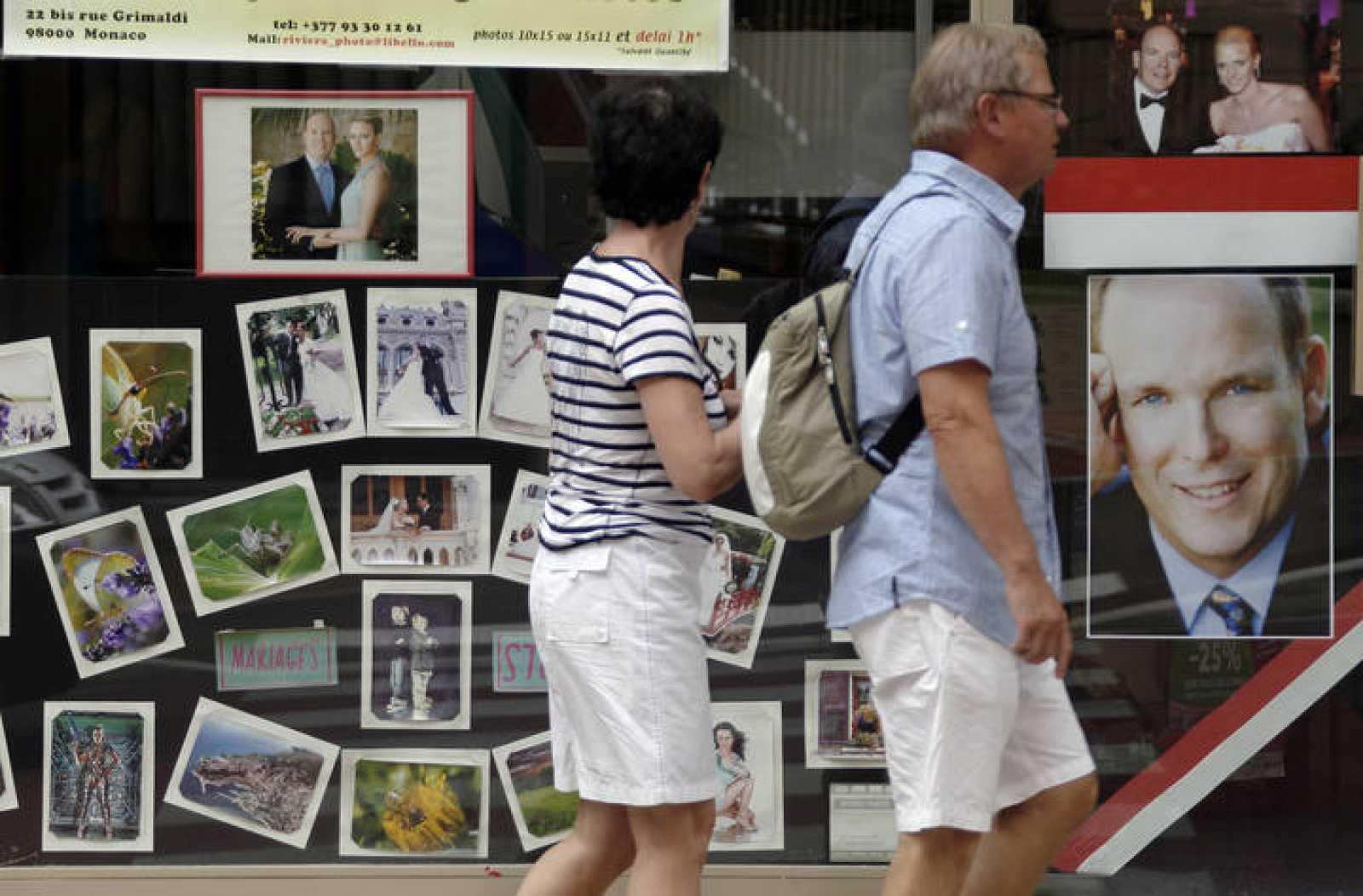 Turistas pasan por un escaparate de Mónaco con fotos de la pareja real.