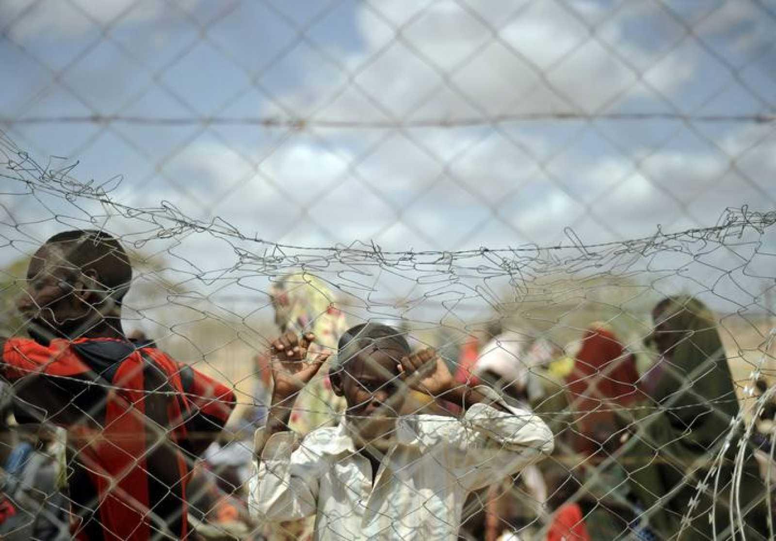 Un niño mira a través de una valla cómo llegan refugiados al campamento de Al Dadaab, en Kenia.