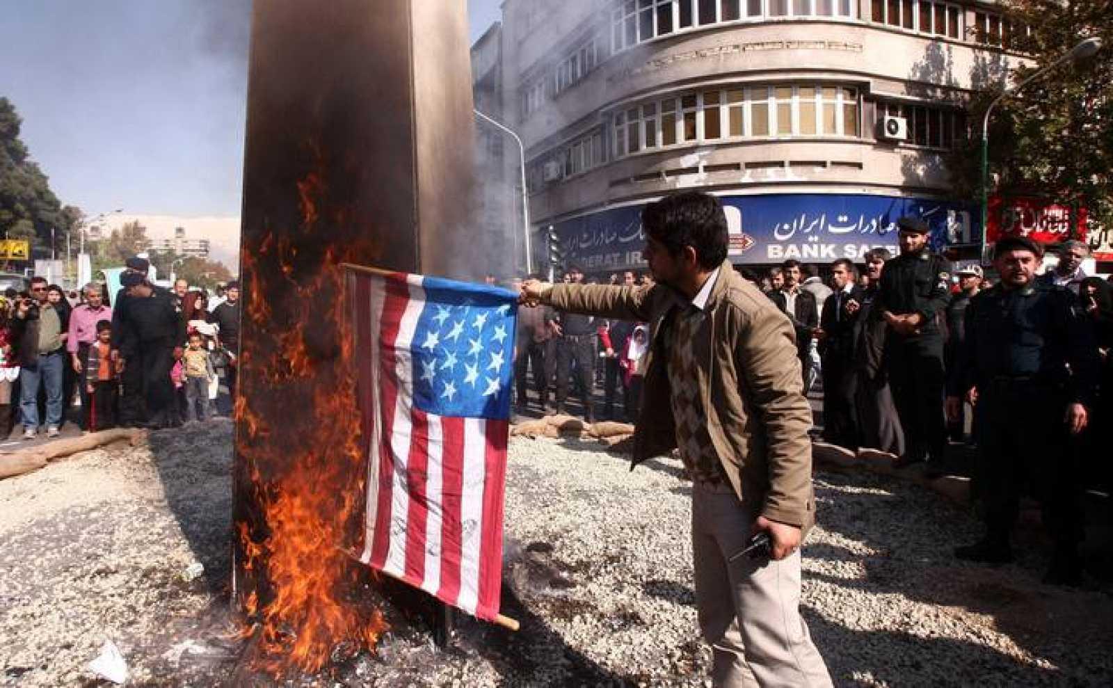 Un hombre quema una bandera de EE.UU. ante la antigua embajada de este país en Teherán