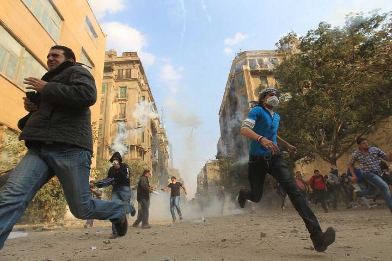 Manifestantes egipcios huyen de los gases lacrimógenos en El Cairo