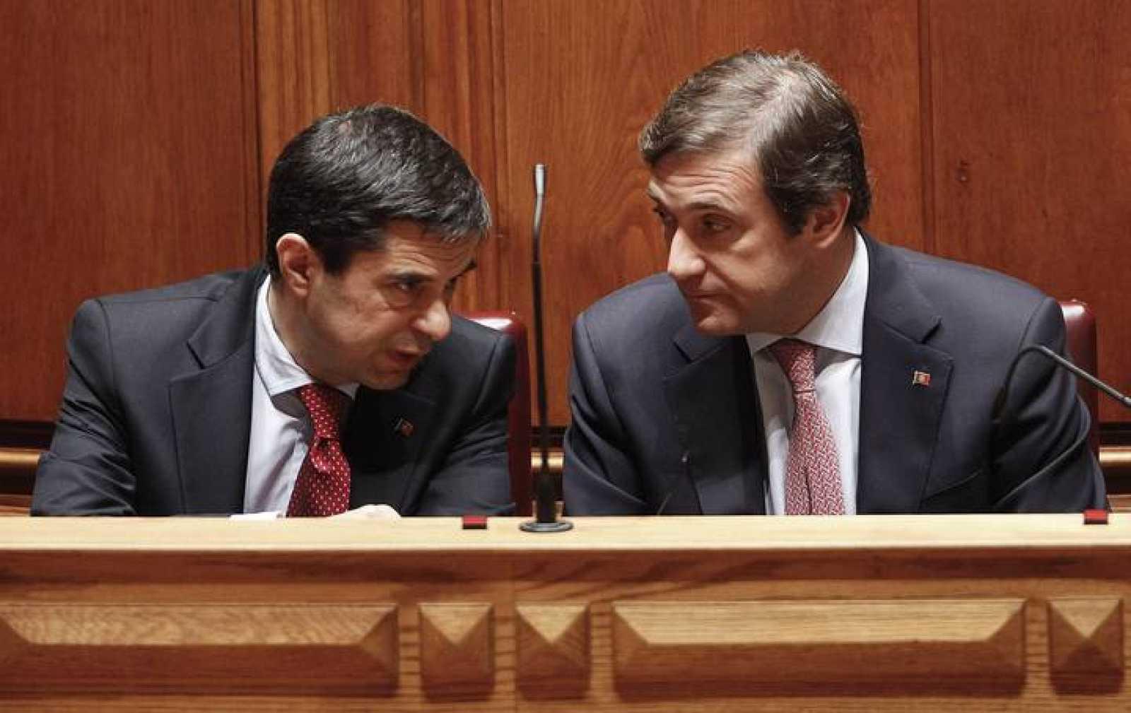 El primer ministro portugués Pedro Passos Coelho (d) conversa con el ministro de Finanzas, Vitor Gaspar, (i), en el parlamento