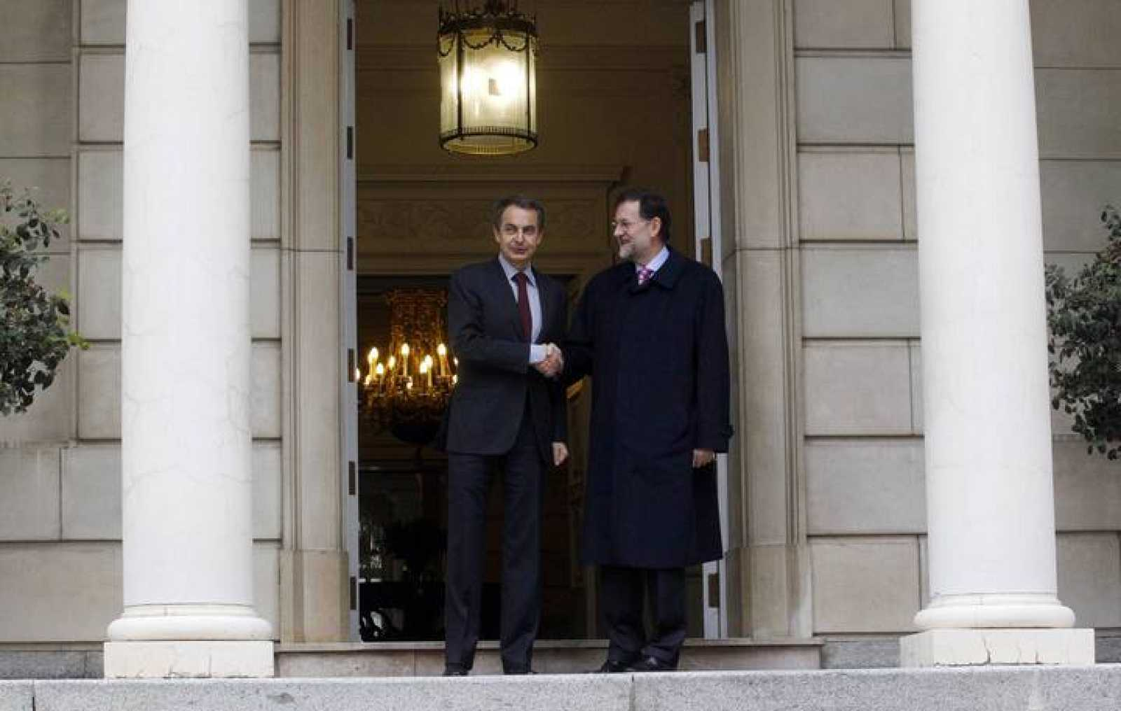 Spain's outgoing PM Jose Luis Rodriguez Zapatero shakes hands with incoming PM Mariano Rajoy during a meeting in Madrid
