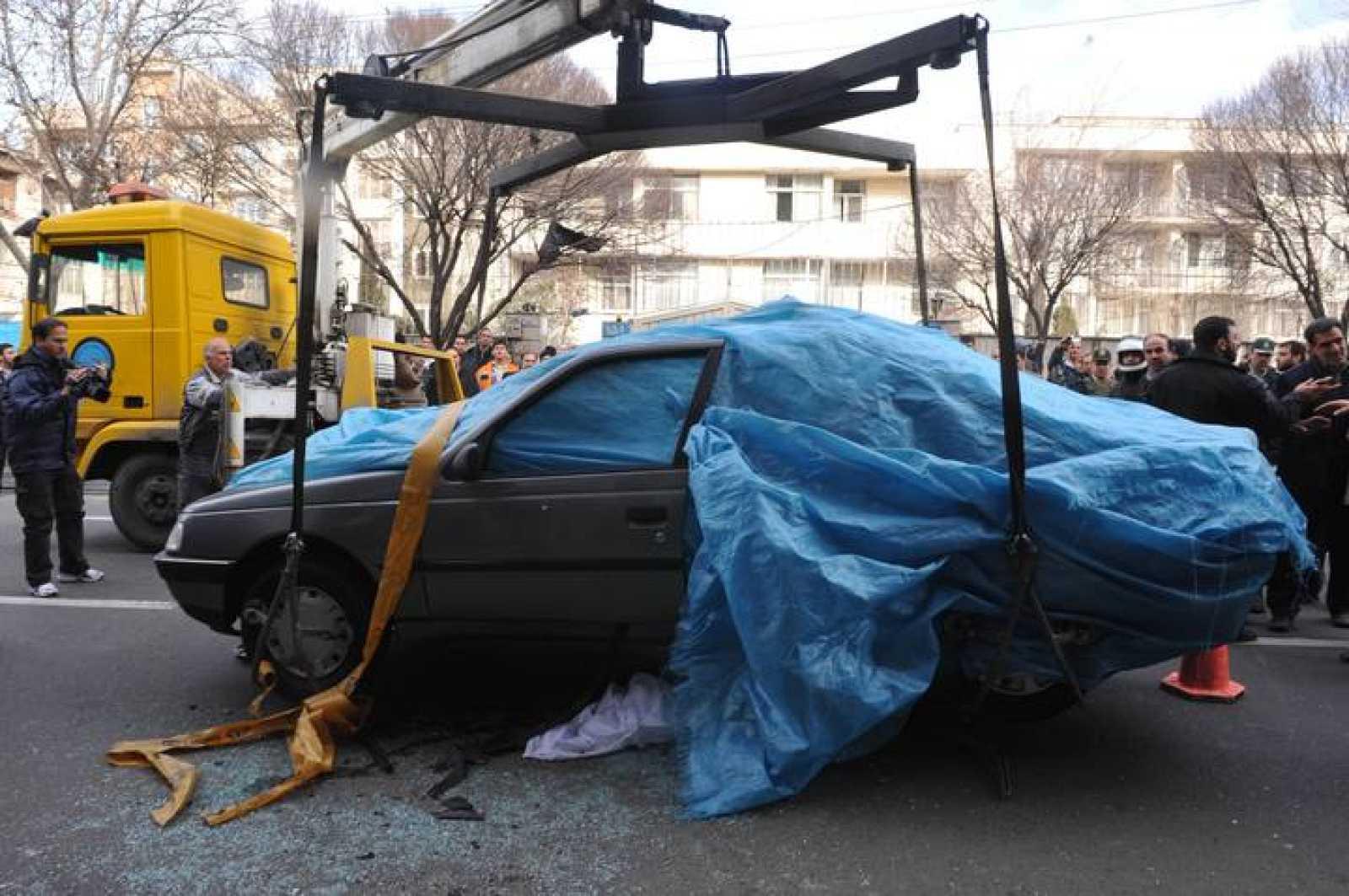 La policía iraní inspecciona el vehículo en el que viajaba un científico nuclear iraní tras explotar una bomba.