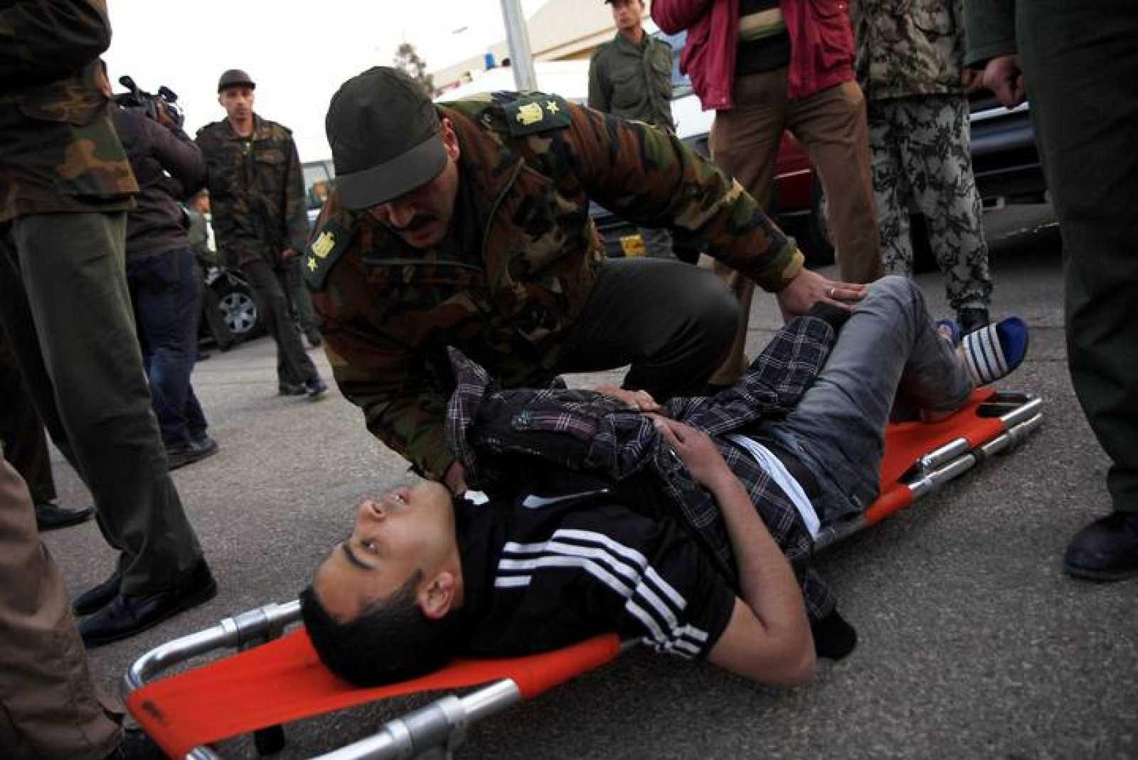 Un soldado egipcio comprueba el estado de uno de los aficionados herido en los incidentes de Port Said a su llegada a El Cairo
