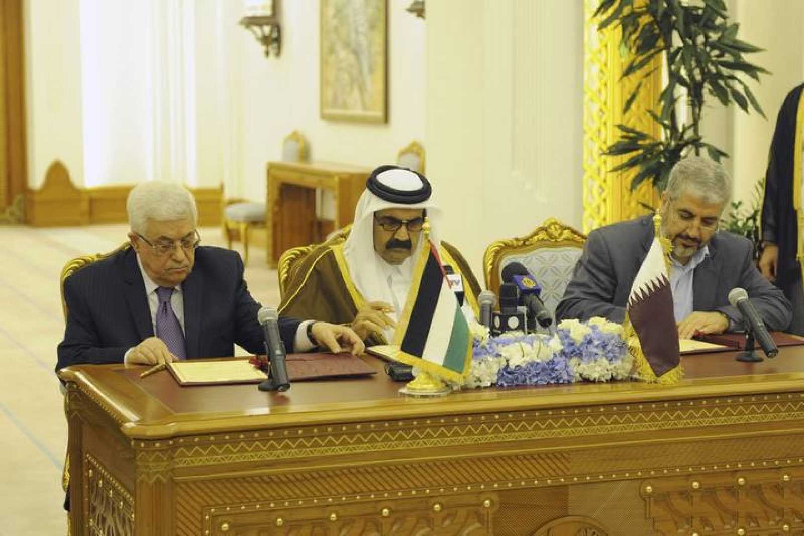 El presidente palestino Mahmud Abás y el líder de Hamás Jaled Meshal firman en Catar