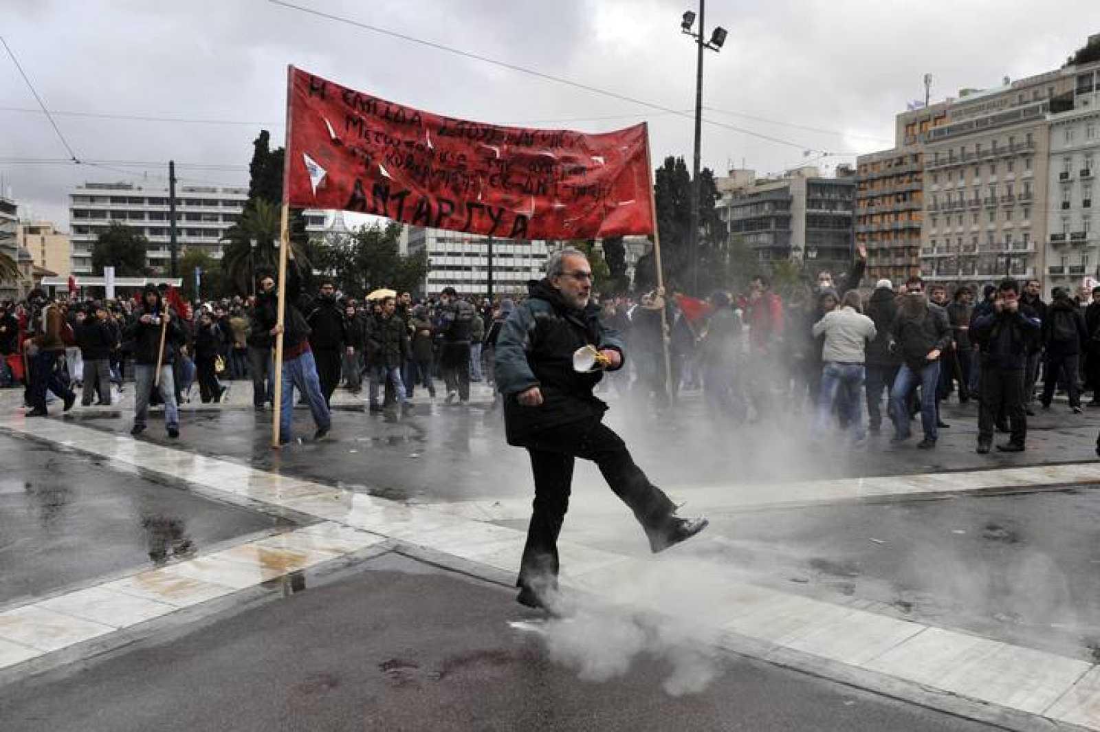 Uno de los manifestantes devuelve un bote de gas lacrimógeno lanzado por la policía a los agentes