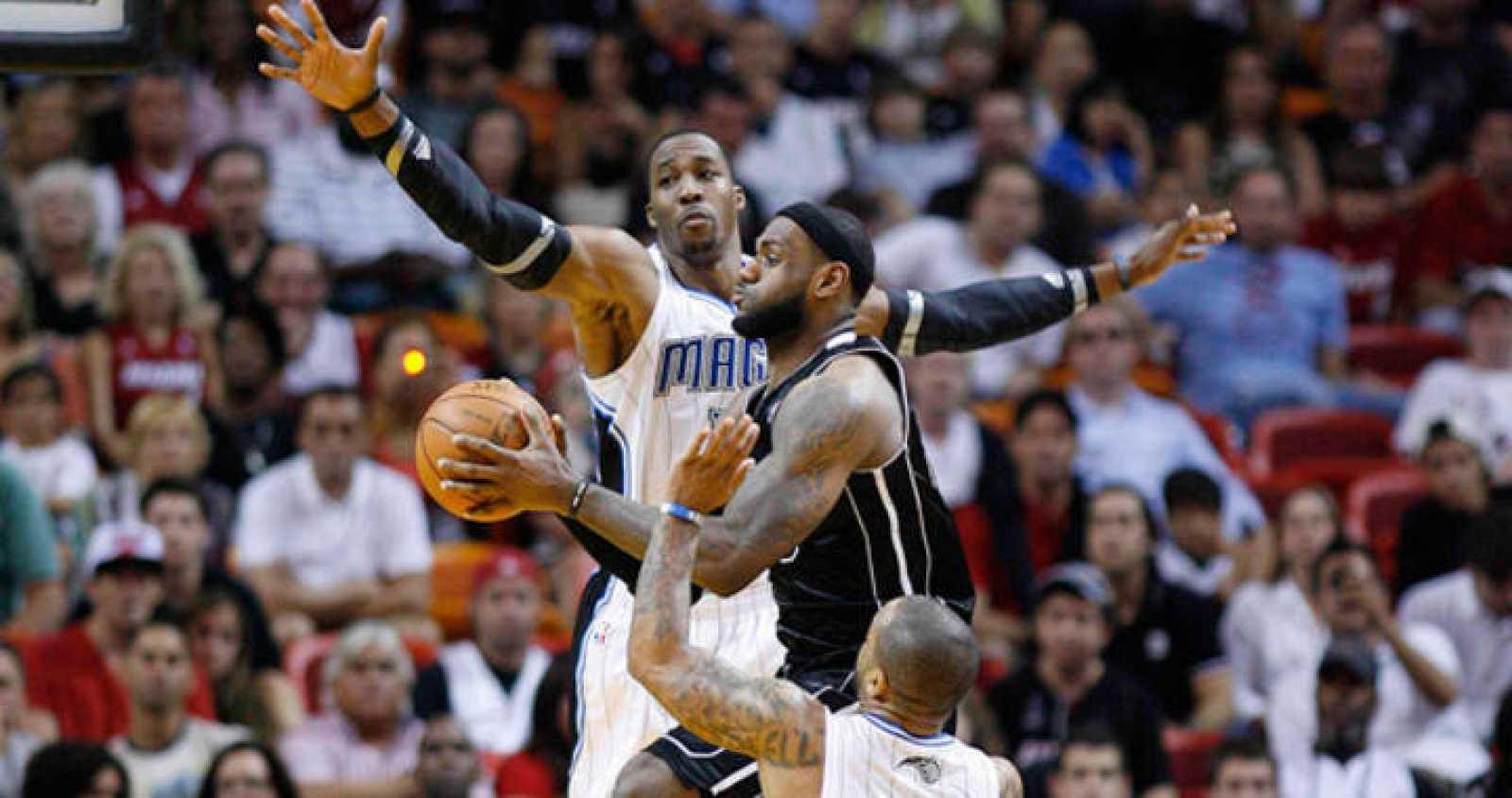 LeBron James intenta entrar a canasta ante la oposición de los jugadores de Orlando, Dwight Howard y Jameer Nelson.