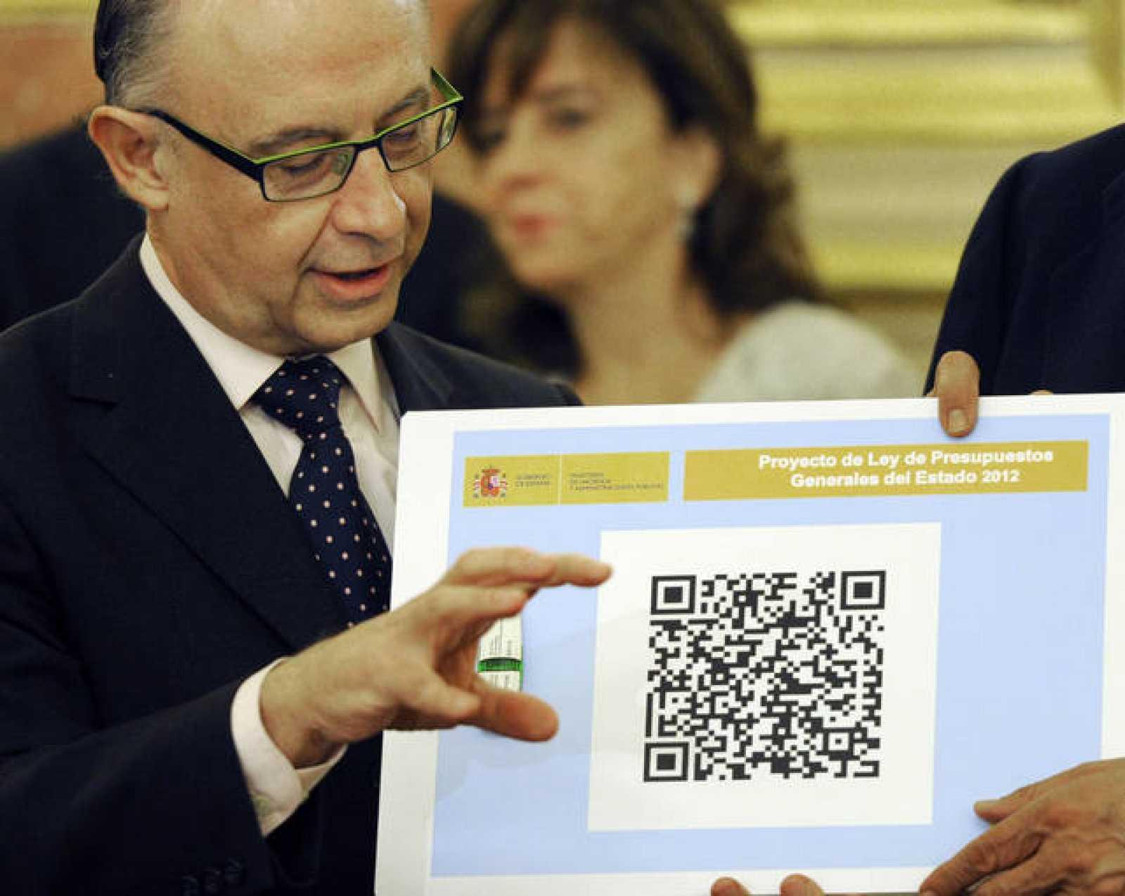 El ministro de Hacienda, Cristobal Montoro, posa junto con el código QR y el pendrive de los Presupuestos Generales del Estado, que fueron presentados este martes en el Congreso de los Diputados