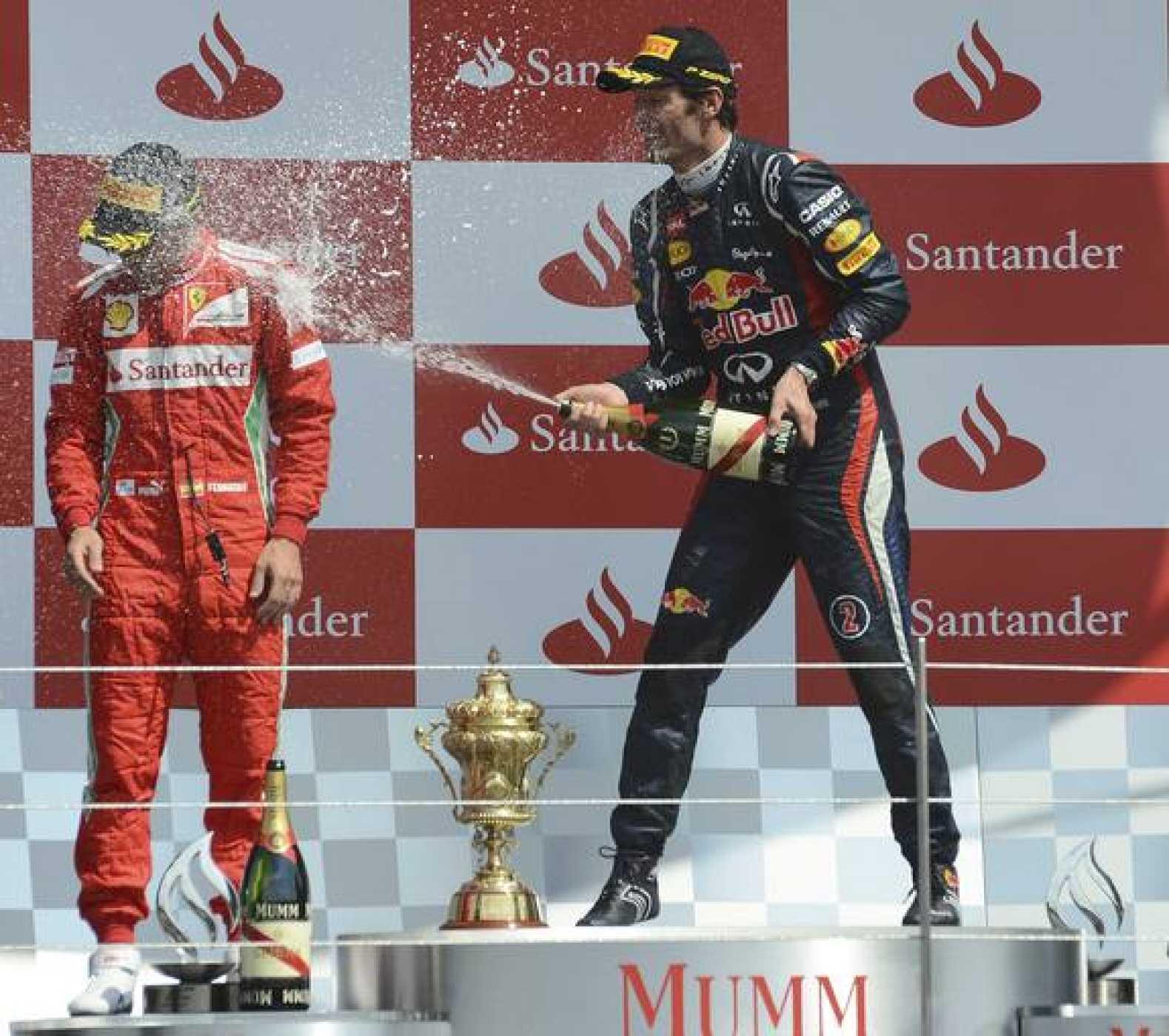 Red Bull Formula One driver Mark Weber of Australia (R) sprays  Ferrari Formula One driver Fernando Alonso after winning the British F1 Grand Prix at Silverstone, central England