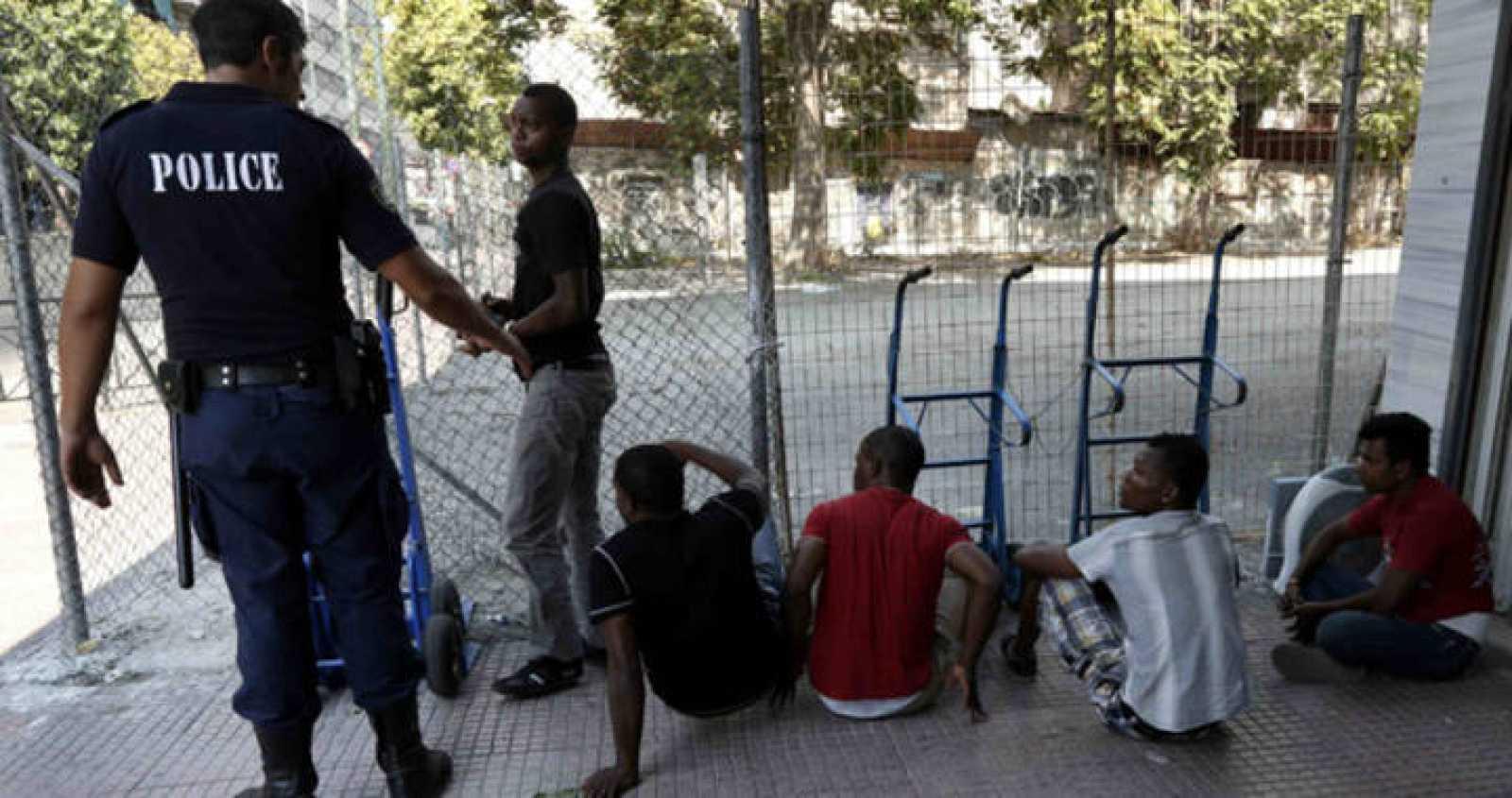 Un policía con un grupo de inmigrantes para comprobar sus documentos de identificación en una de las redadas policiales contra la inmigración ilegal en Atenas el 14 de agosto.