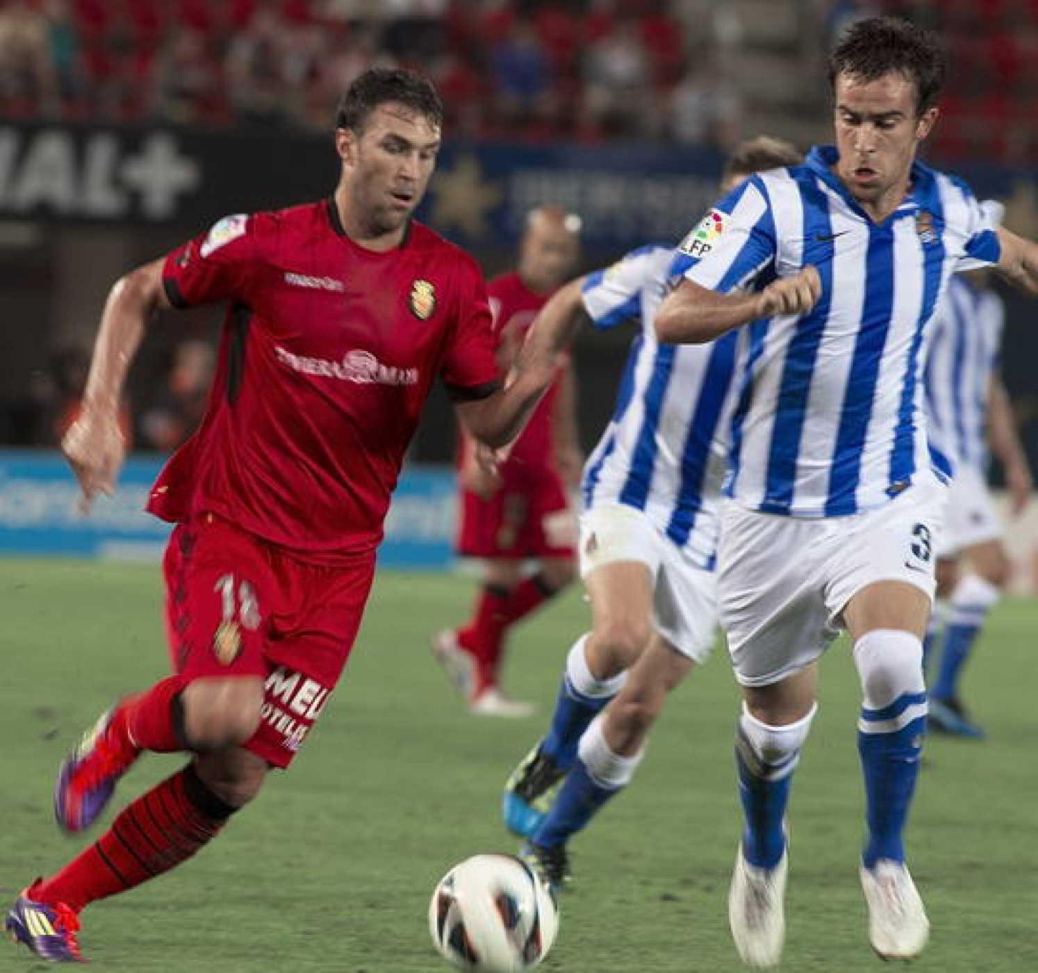 El delantero del RCD Mallorca, Víctor Casadesus (i), disputa el balón con el defensa de la Real Sociedad, Mikel González
