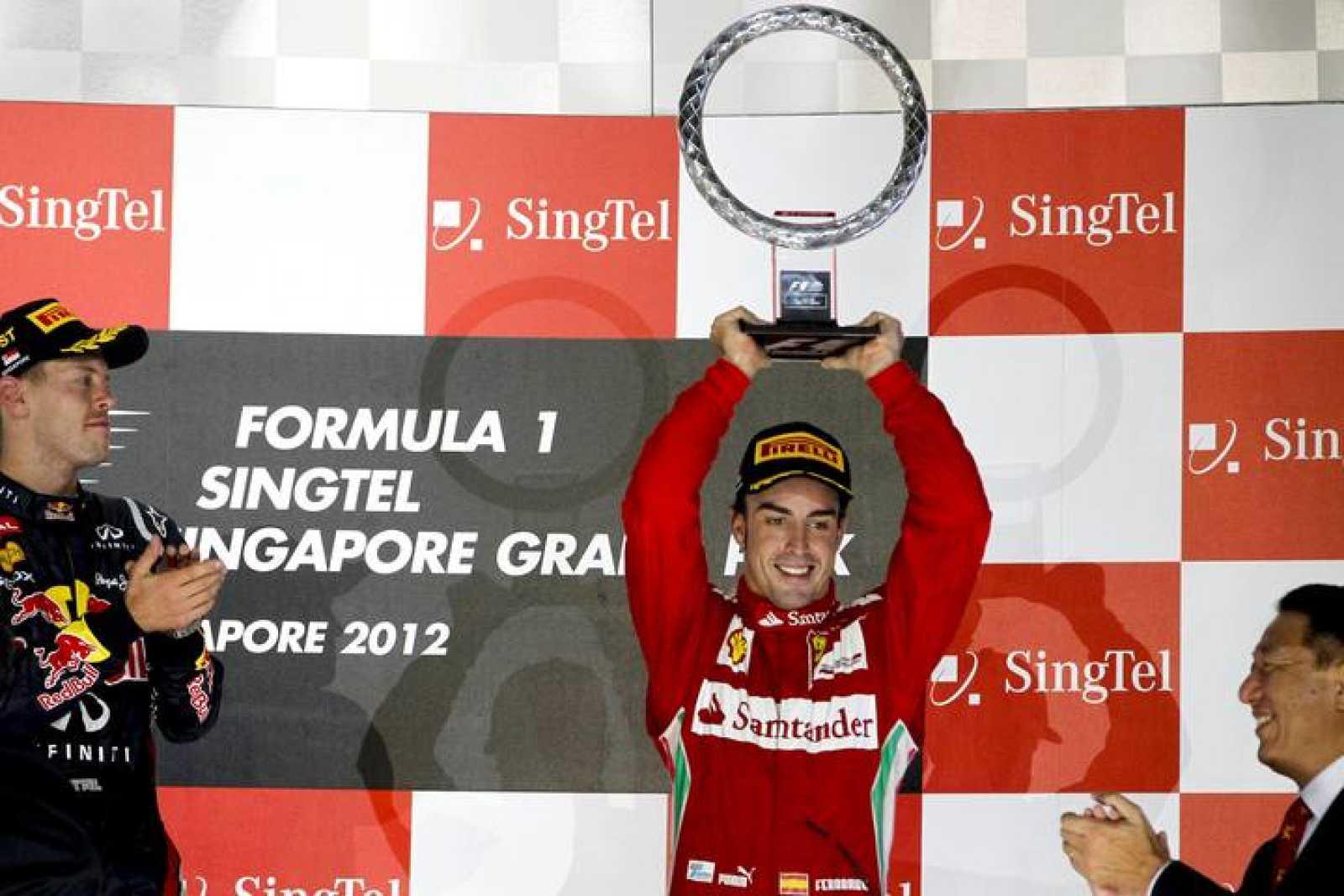 El piloto español de Fórmula Uno Fernando Alonso sostiene su trofeo después de finalizar en tercera posición en el Gran Premio de Singapur.