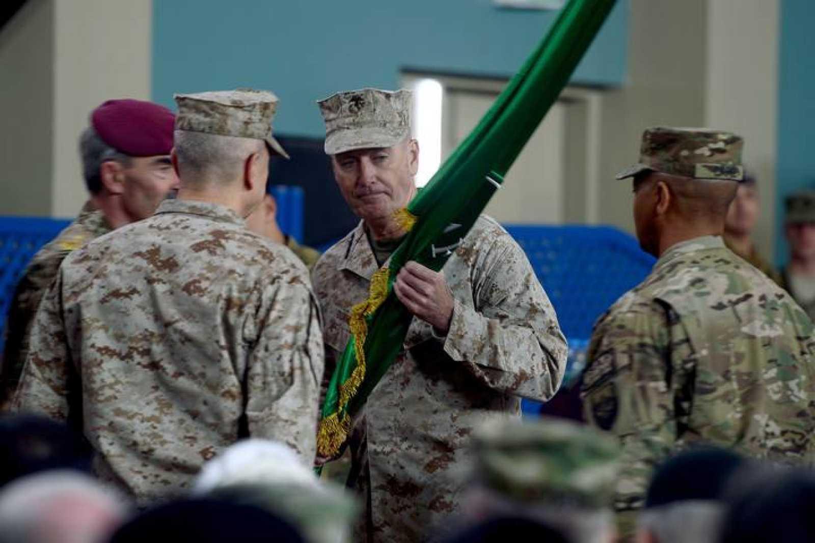 El general Joseph Dunford recibe una bandera durante la ceremonia de traspaso de poderes al mando de la ISAF en Kabul