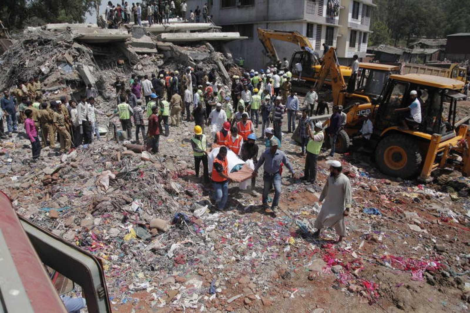 Miembros de los servicios de emergencia transportan el cadáver de una de las víctimas tras derrumbarse un inmueble de construcción ilegal en la localidad de Thane, próxima a Bombay.
