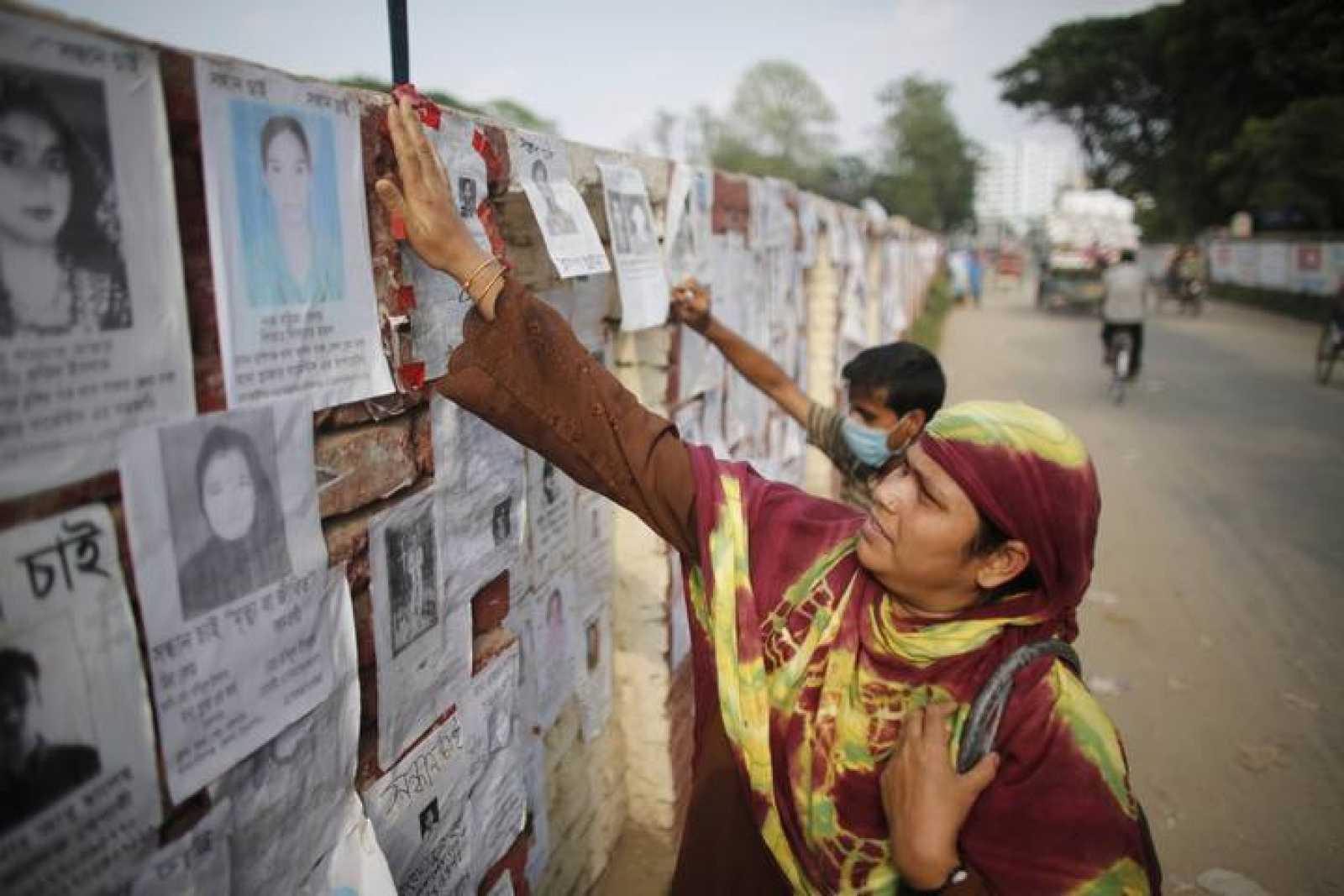 Una mujer comprueba la lista de nombres de desaparecidos por el derrumbe del edificio en Bangladesh