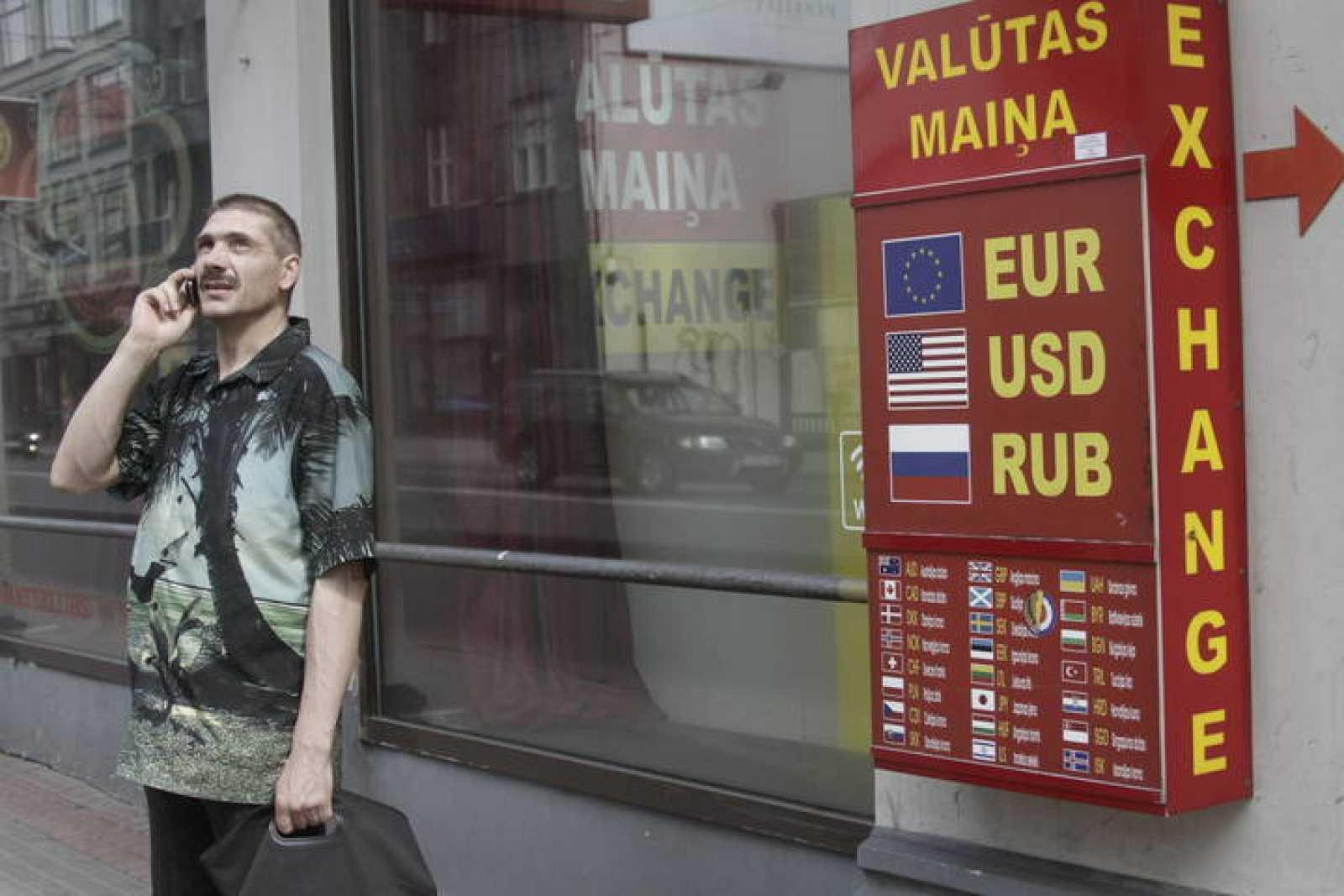Un hombre permanece junto a una oficina de cambio de moneda en Riga