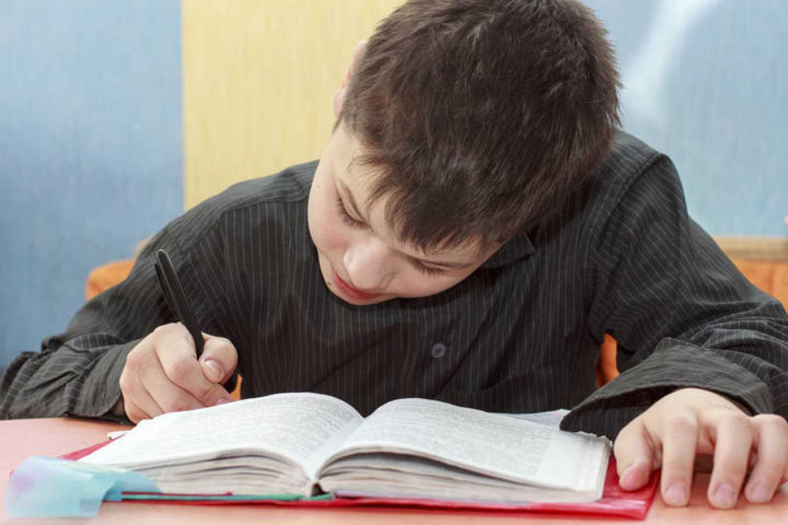 Niño haciendo los deberes con un libro de texto.